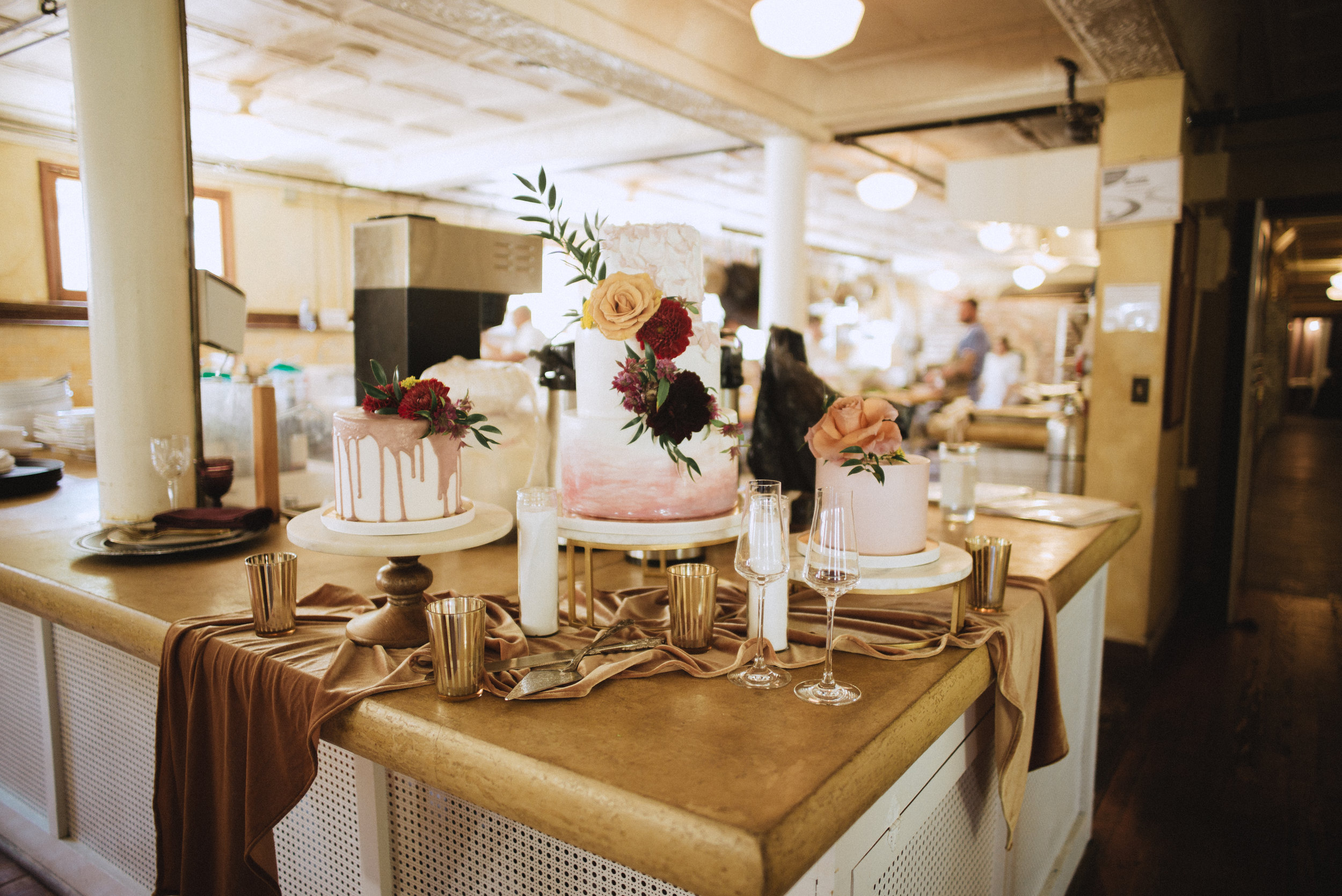 Gold and vintage wedding cake table with flowy silk table runners