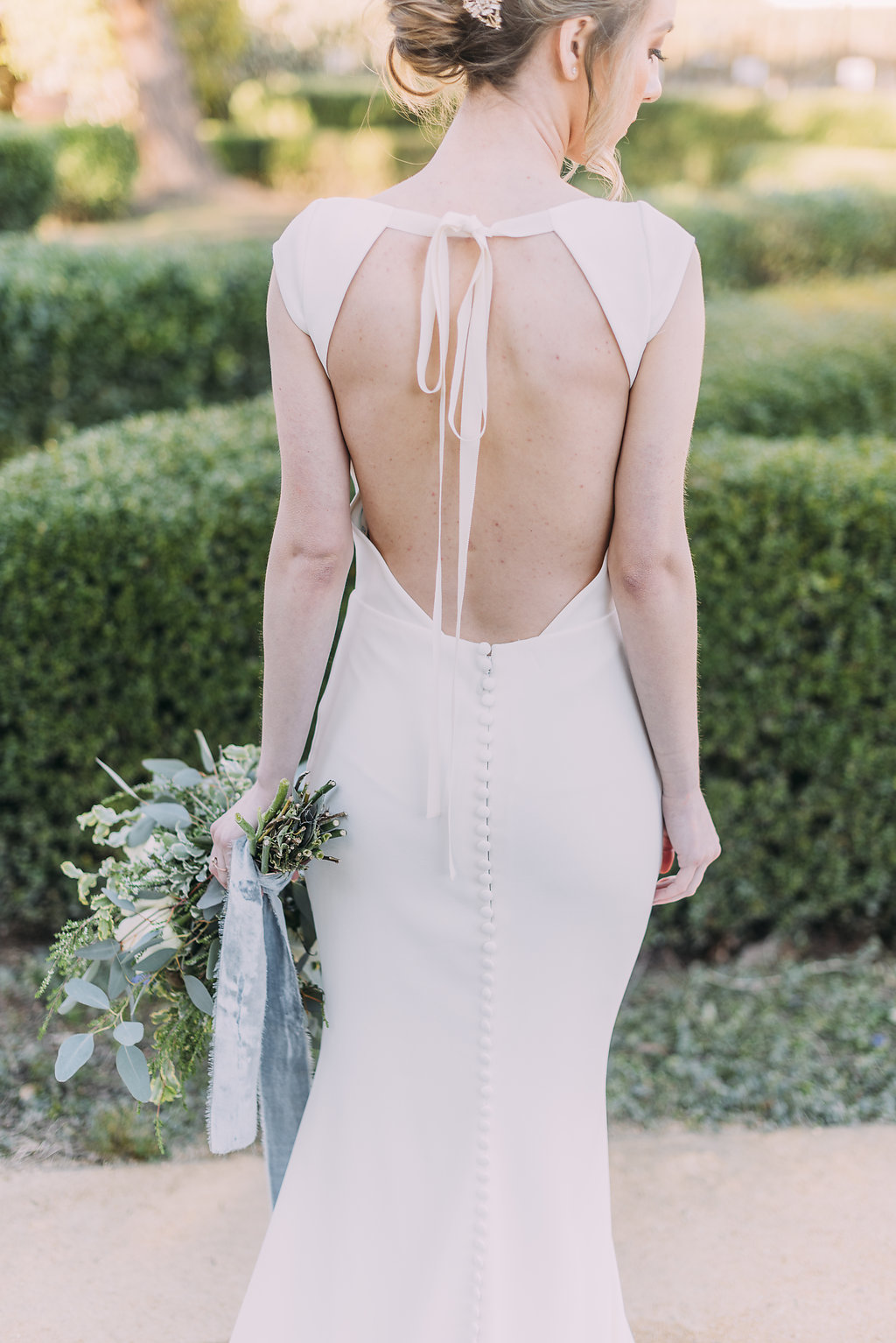 bridal dress with gorgeous back details and pretty bridal bouquet with white and green silk ribbons