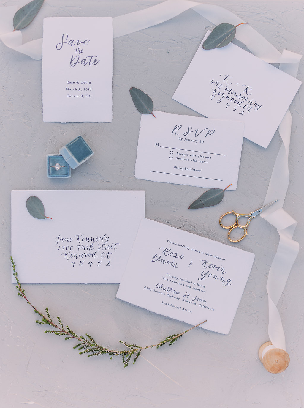 white themed french wedding invitation calligraphy flatlay with white silk ribbon