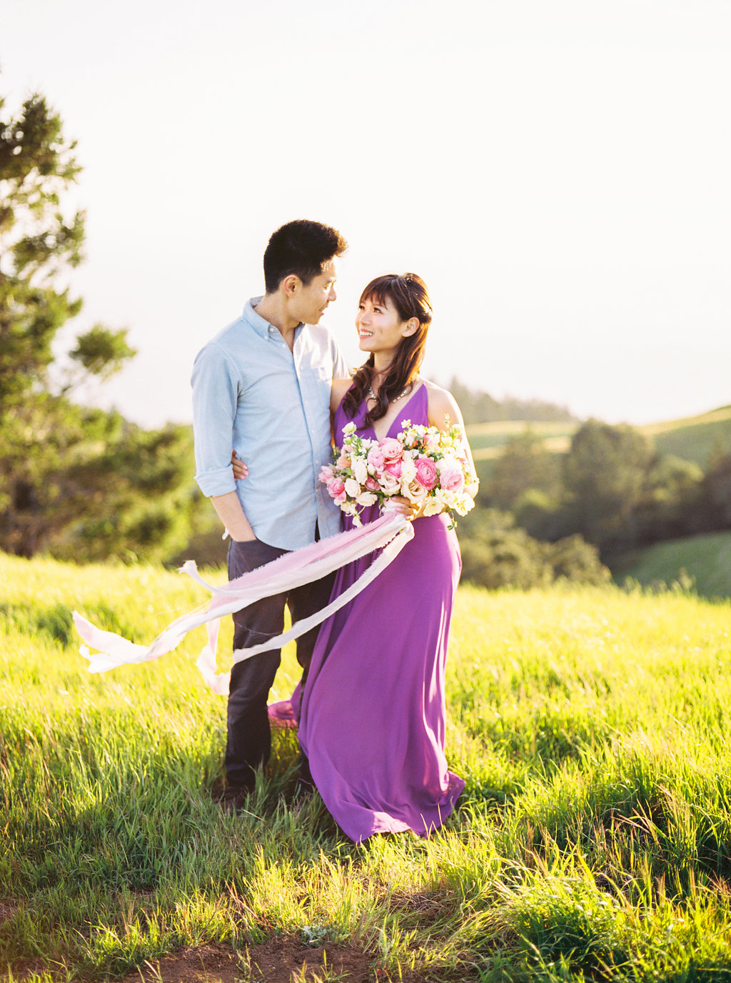 Engagement shoot on grassy hills with violet dress and pretty floral bouquet with white and lavender silk velvet ribbons