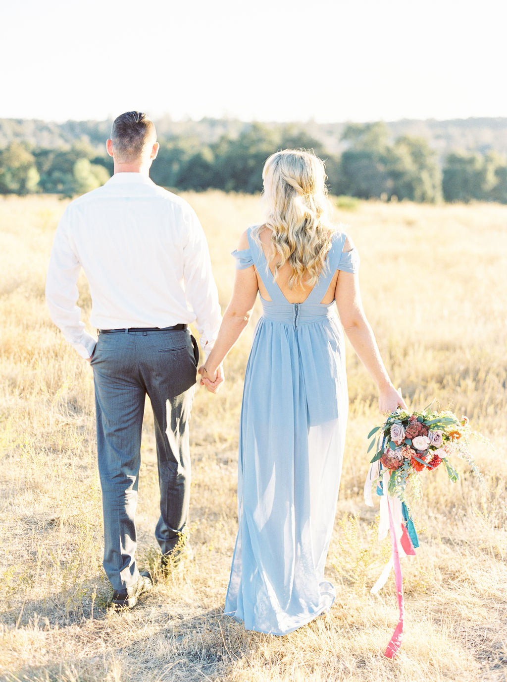 Pretty and dreamy engagement Photo featuring colorful floral bouquet with silk velvet ribbons