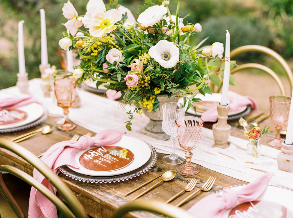 Pink wedding tablescape with pink napkins, table runner, and gold tableware for outdoor spring wedding