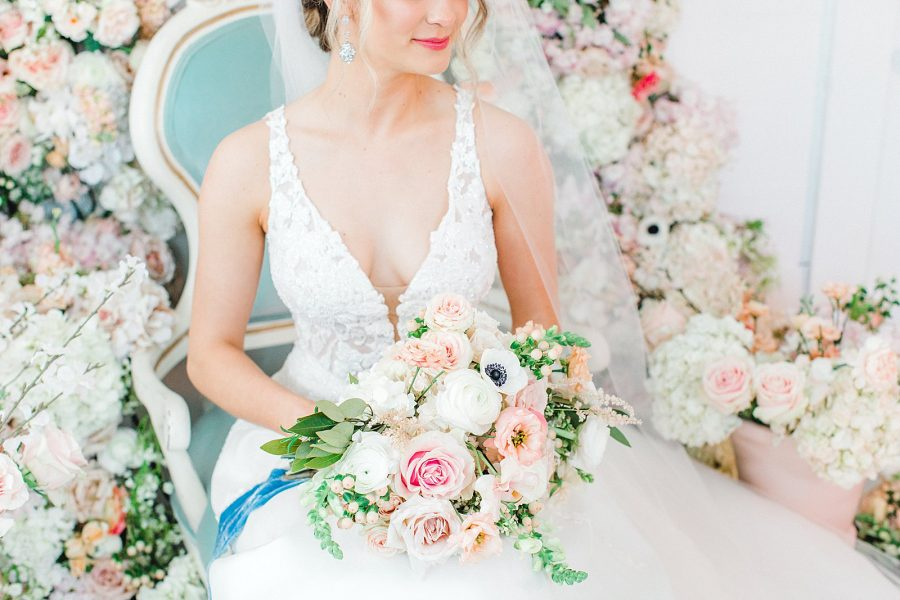beautiful bridal gown and bouquet with blue silk velvet ribbons on a floral installation background