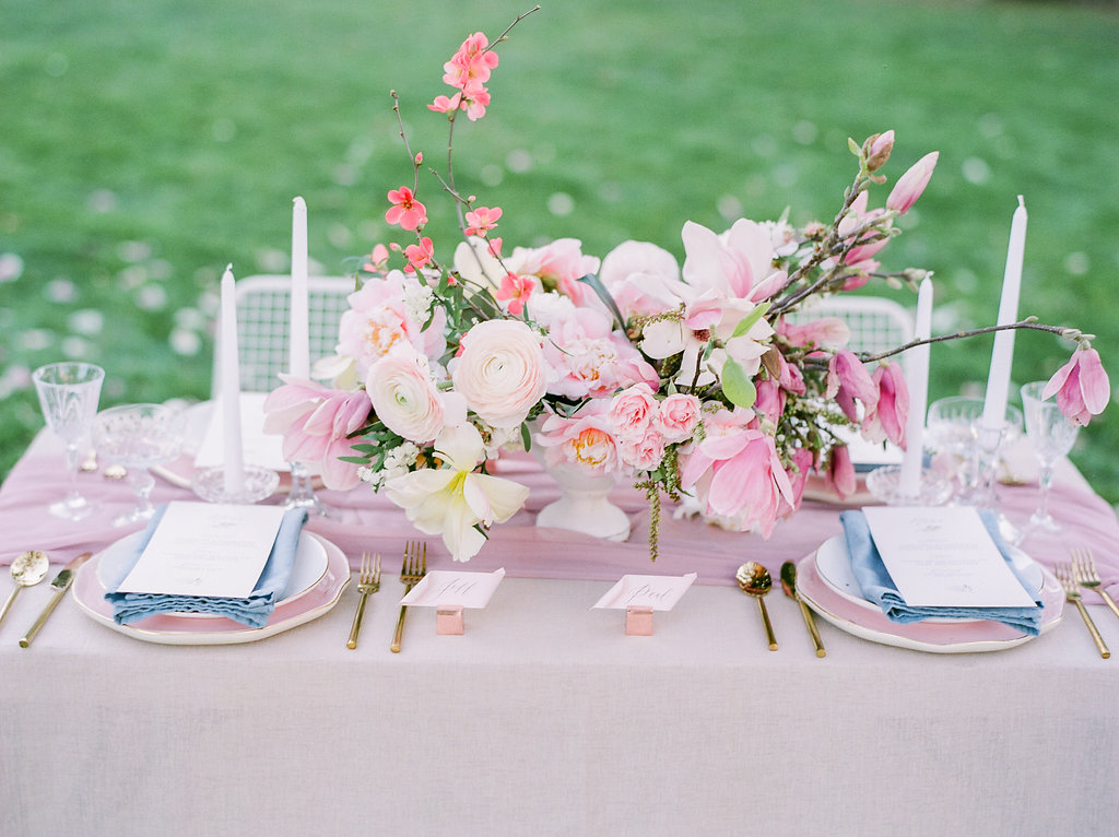 Pink wedding tablescape with gorgeous floral arrangements,silk table runners, and tableware