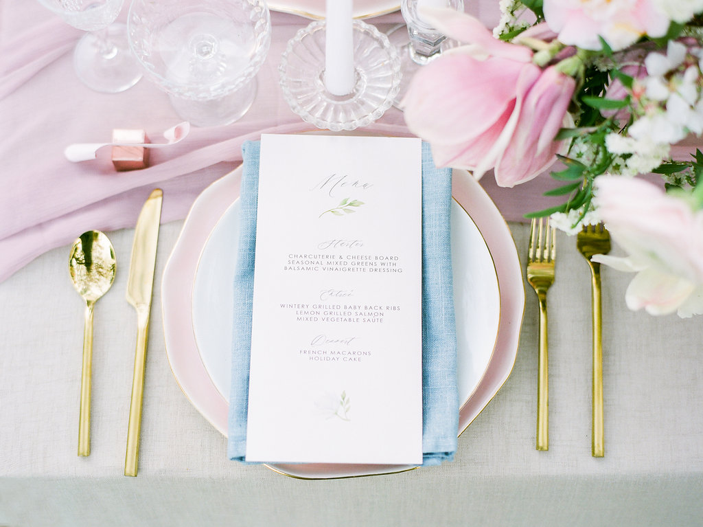 Pretty table setting details with blue table napkins and gold cutlery