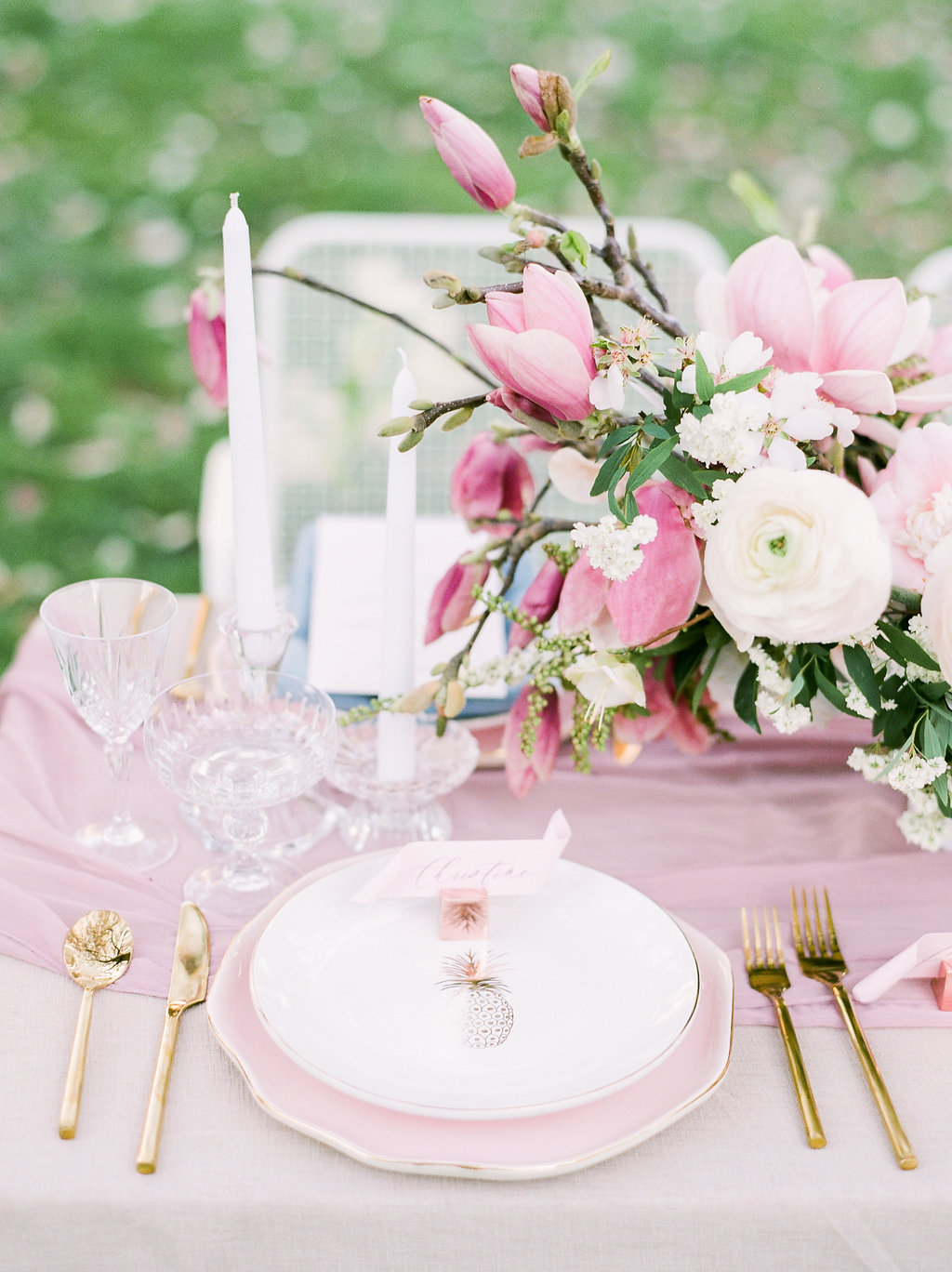 Pink silk table runners and Floral arrangements with gold cutlery for wedding tablescape idea