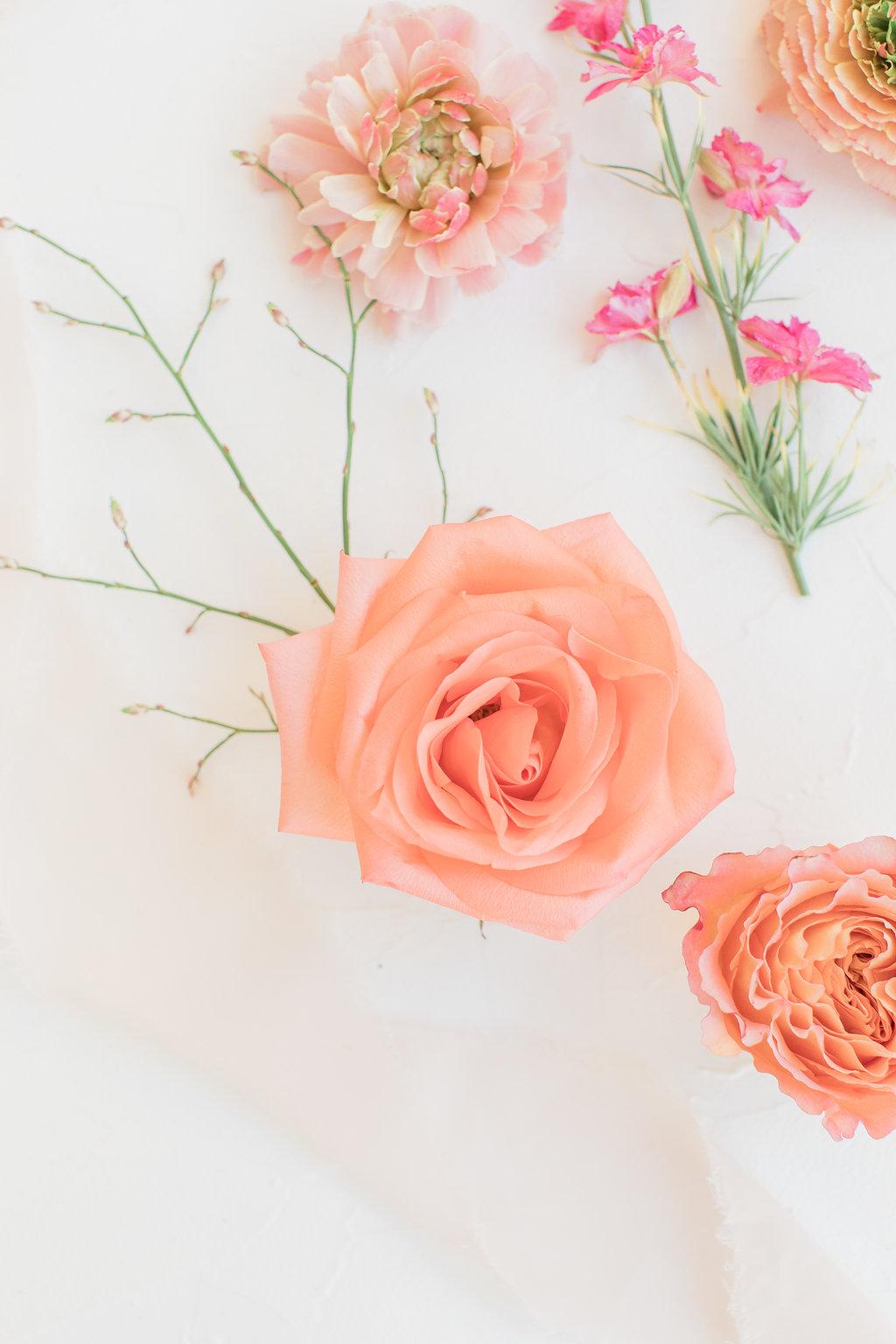 Pretty peach floral flatlay with silk ribbon