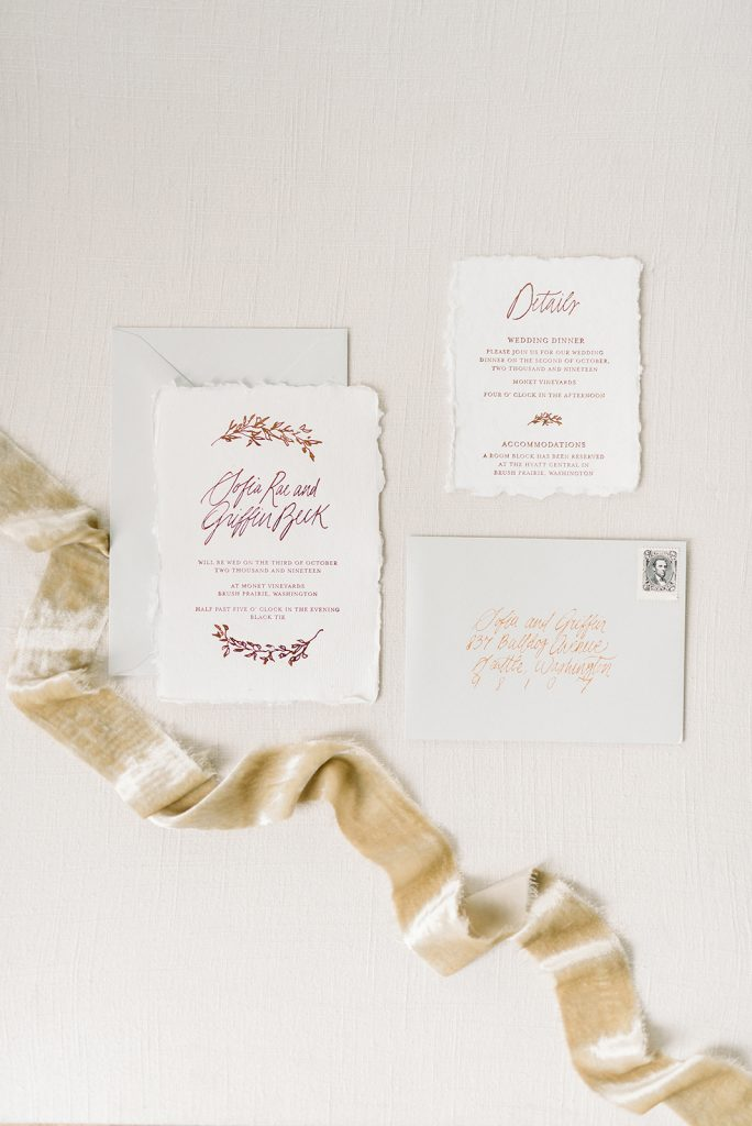 Pretty, simple, and classy wedding calligraphy invitation flatlay with silk velvet ribbons