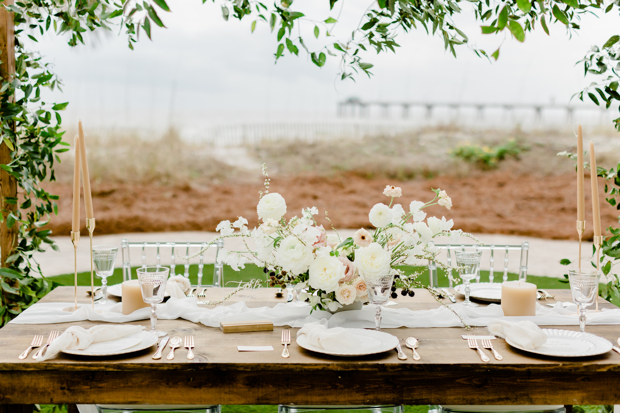 pretty wooden table for outdoor weddings with gorgeous floral centerpiece and flowy silk table runners