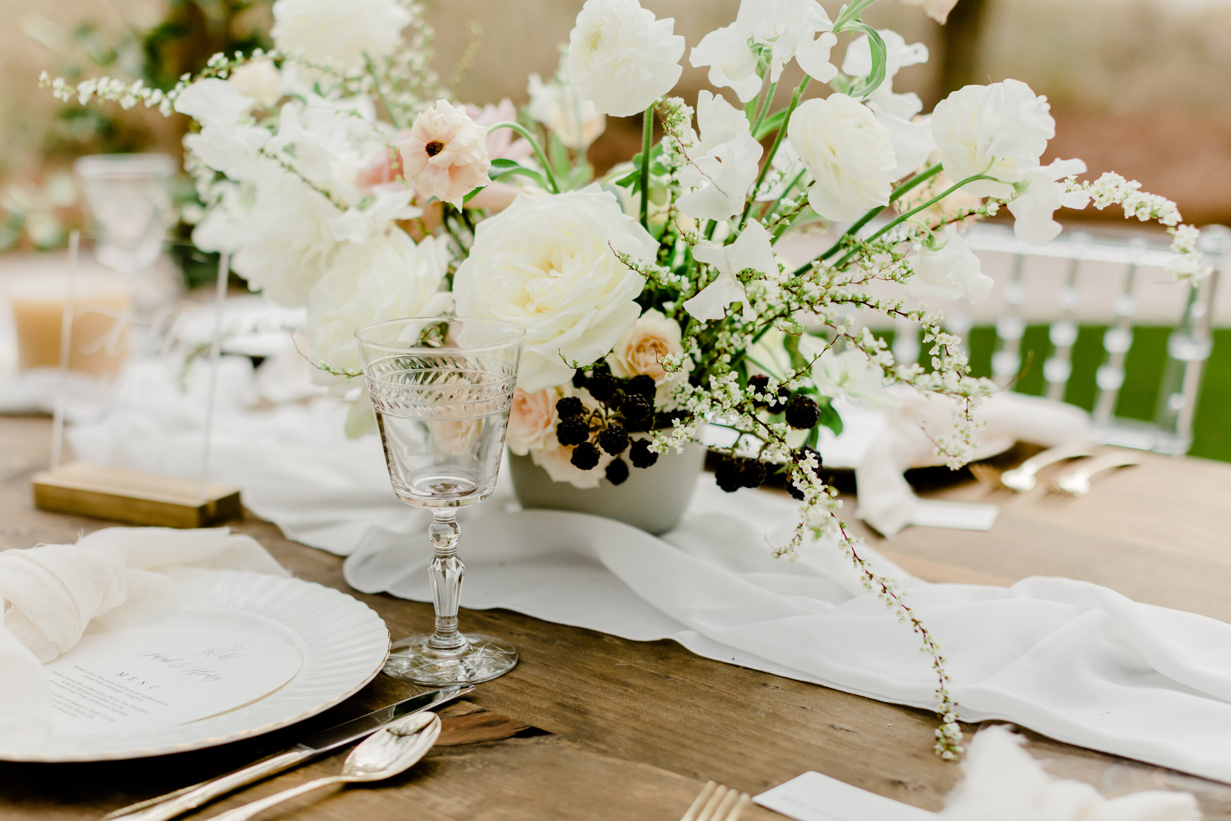 beautiful white tablescape for sophisticated and elegant dreamy wedding with flowy silk table runners and floral centerpiece