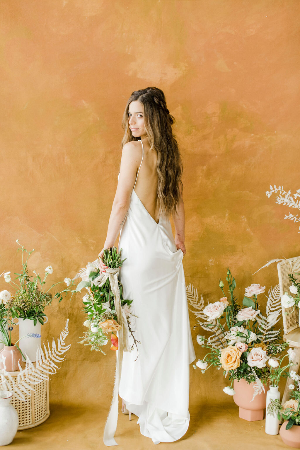 gorgeous backless wedding dress and curly braid hairstyle for bohemian wedding with silk ribbon floral bouquet