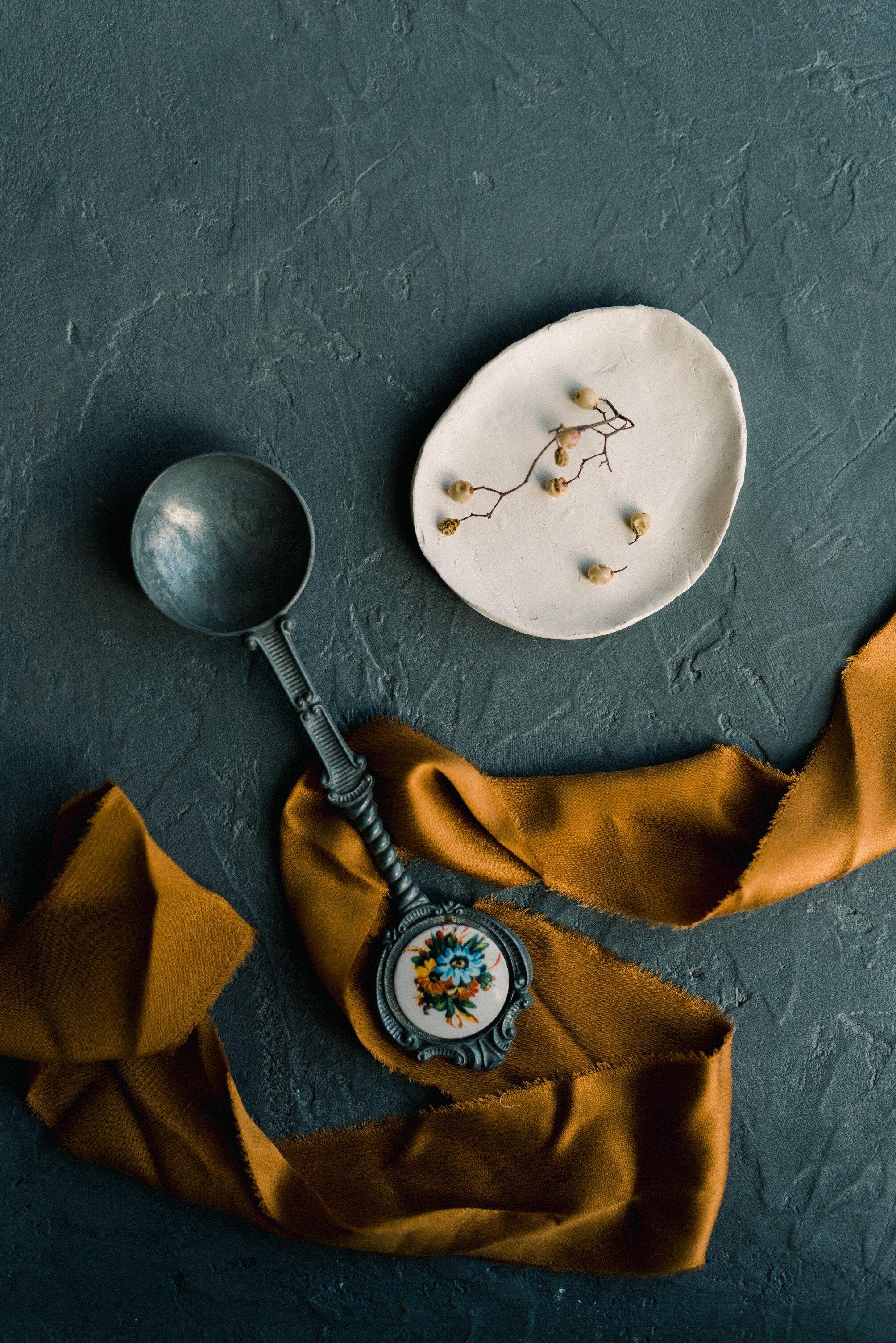 Amber golds, dark blue greens, and off white wedding accessories on elegant silk ribbon flatlay