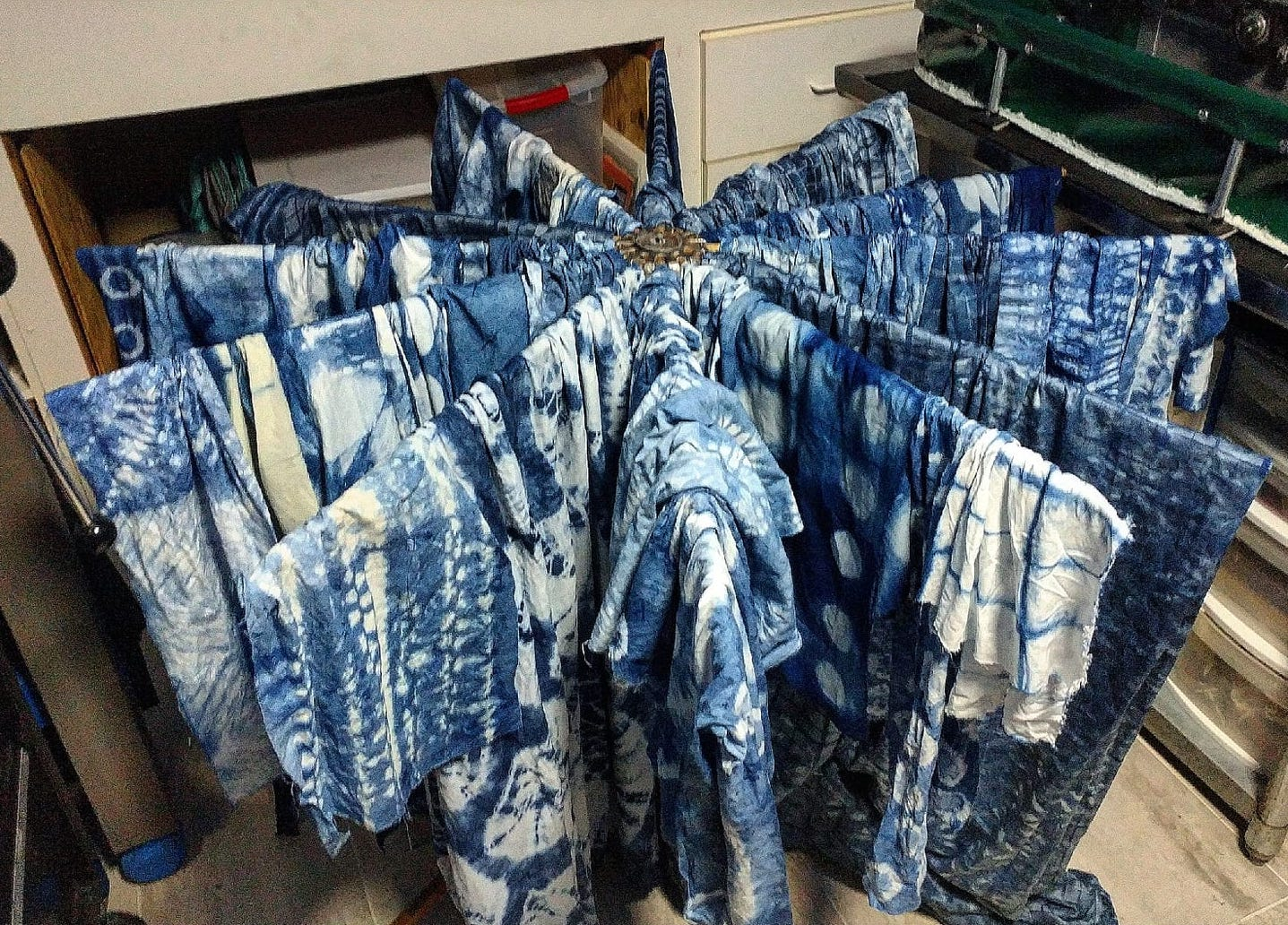 Over fifty pieces of shibori-dyed fabric drying.