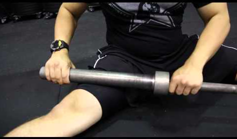 Sit on the ground with a 45# barbell. Focusing on one quad at a time, begin to roll the end of the barbell up and down your quad in a smooth, slow motion. Find the sticky, junky, sweet spots and roll back and forth on them. Try approaching your leg from a straight-on position as well as along the outside and inside. You can easily hit your vastus medialis oblique (VMO), the muscle on the inside of your thigh, closest to your knee and always a sweet spot. You can also turn your leg in so to dig into your illiotibial band (IT band), which runs from your hip down to your knee. My fave is my rectus femoris, which is located up at the top and just ever so slightly off from the center line. You'll know you hit it because it will feel like you're smashing your femur and honestly you are. Spend at least a good three to five minutes on each leg and longer if you have the time. Smashing is a great cool-down post-WOD. This can also be done with a rolling pin if a barbell is not available (wash after use before you make your pie crust).