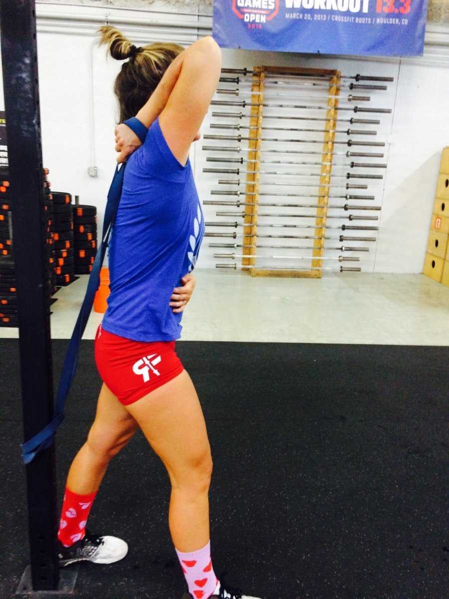 One of the limiting factors in our front rack position is whether or not we even have the range of motion (ROM) to lift our elbows high enough on their own. Tightness in the triceps and lats can inhibit the high elbow positioning.  In this stretch you will attach a  resistance band  to the base of the rig. The height of your resistance band will depend on how strong the band is, how tall you are, and how insanely inflexible your triceps are. While facing the rig, wrap the resistance band around your wrist and hold on to it. Turn your body to face away from the rig while bringing your bent arm over head. Work to keep your arm and shoulder externally rotated just like in the last exercise, and try to keep your palm faced towards your head/the ceiling. Keep your elbow close to your head and do not over arch your low back. We always want stability in the lower spine and mobility in the upper. Hold here for one to two minutes before  GENTLY  releasing and switching sides.