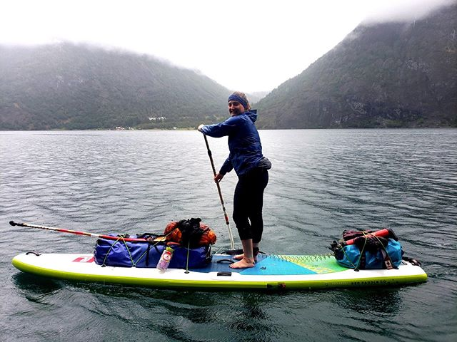 With so much rain we skipped our lunch spot swim on this day. I recall catching myself many times from falling into the fjord on the last few km as my waterlogged hands lost grip and slipped down the paddle as I dropped my weight down onto the blade 😬  Although we kept fairly warm while paddling the chills could sneak up on us quickly when pausing for a break or upon arriving to shore ☔️ On these wet days it is especially important to put up shelter immediately, to change into warm/dry clothes, and to get some food and drink down. (I imagine that my body temp was good here without Goretex pants but that I put them on over dry pants as soon as I hit shore)  With large amounts of rainfall keeping gear dry and maintaining warmth can be a challenge but as we were prepared and could manage ourselves wisely we were set up well to experience a meditative paddle through raindrops, to hear waterfalls come to life, and to soak in the beauty of fleeting rainbows.  @supnorway 📷 @standup_paddle_duck