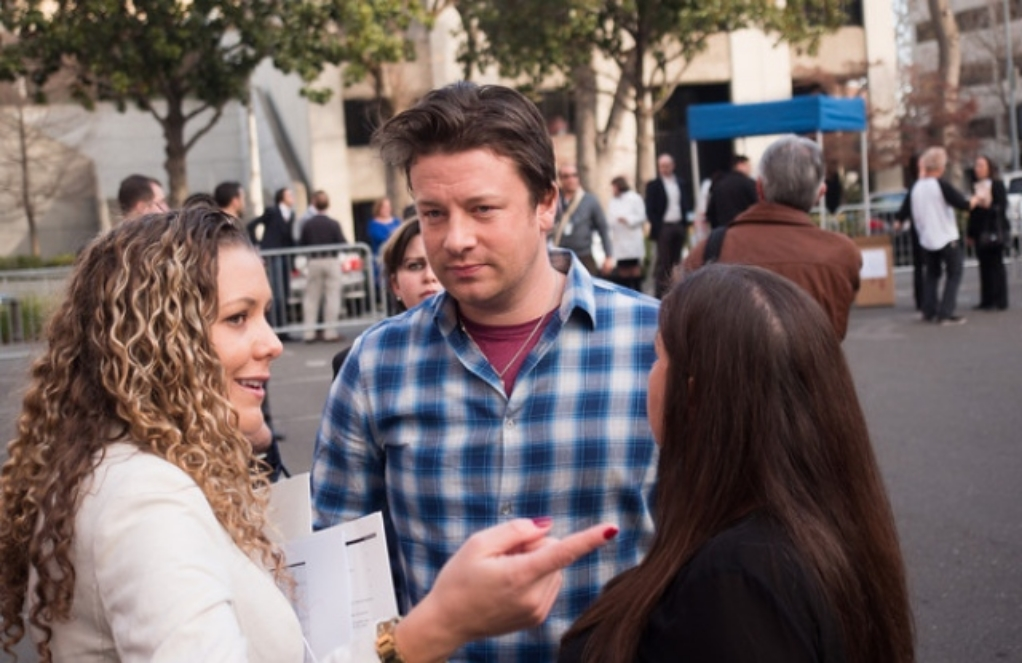 SGS CEO Kate Azar gives celebrity Chef Jamie Oliver a logistics brief before he takes the press conference stage to discuss his efforts to bring healthier school meals to California.