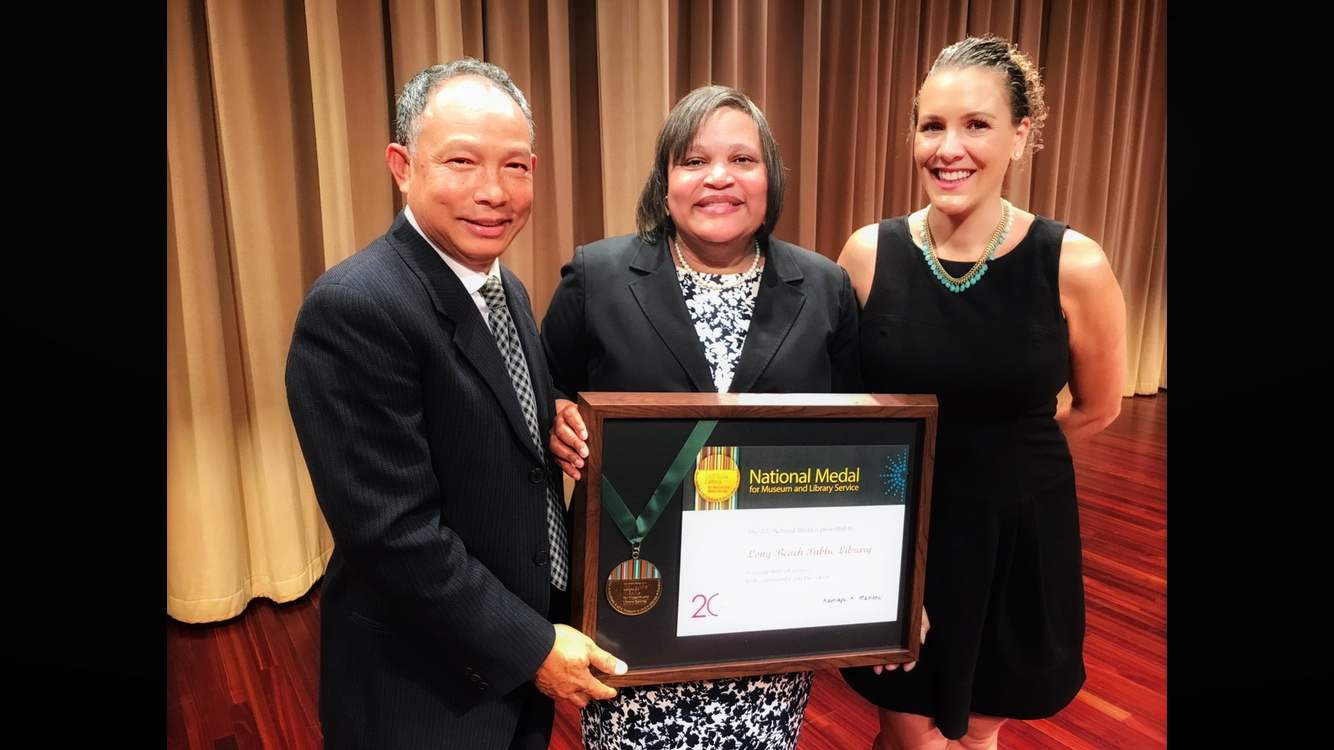 In 2016, the Long Beach Public Library won the National Medal of Museum and Library Services. Kate is pictured here in Washington, DC with Long Beach Director of Library Services, Glenda Williams who is holding the medal, and Library volunteer, Bryant Ben (left).