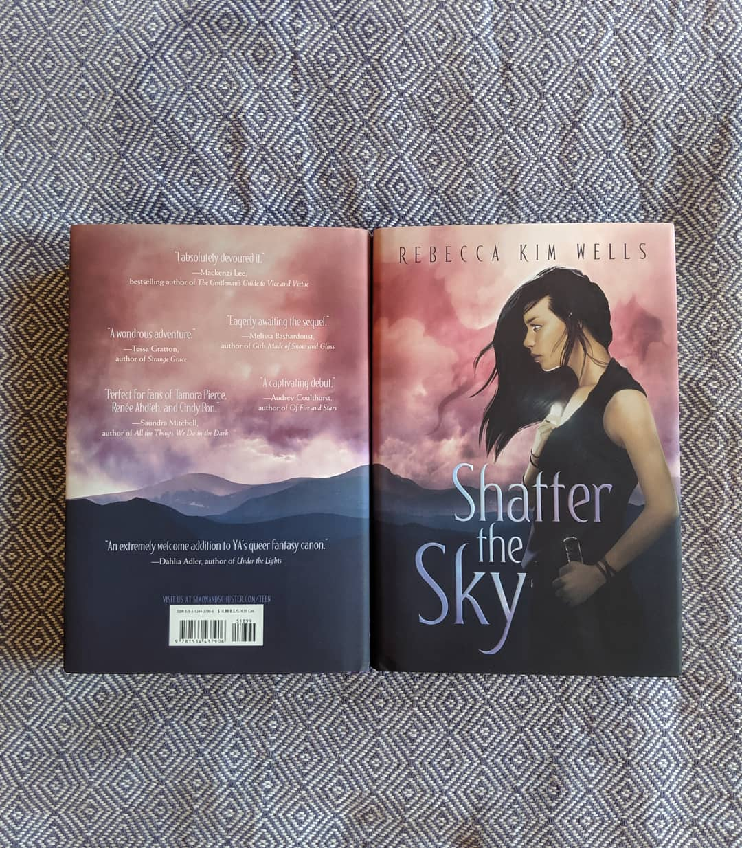 Two finished copies of SHATTER THE SKY, displayed over a blue and white fabric.