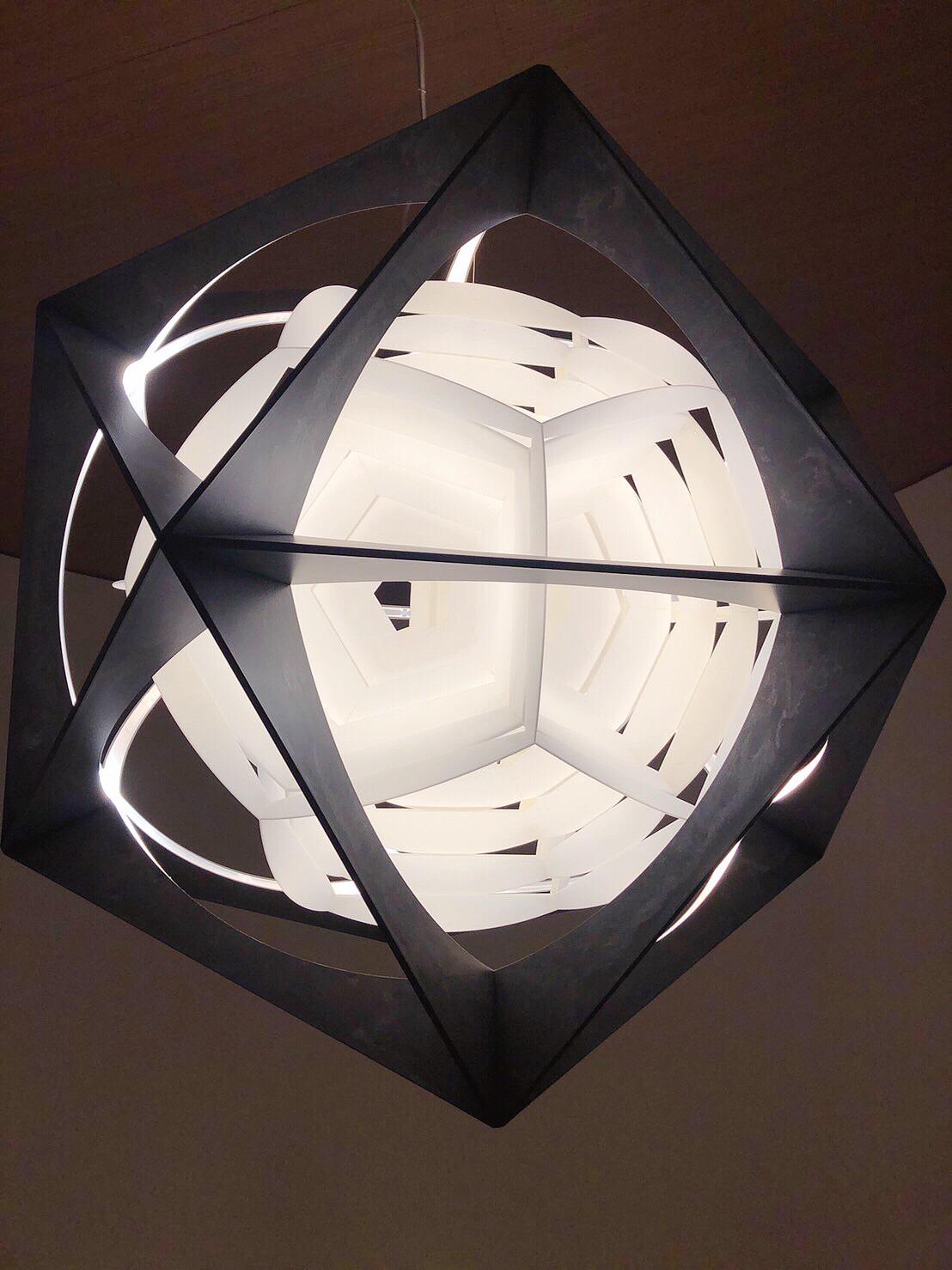 OE QUASI 吊燈 - 設計師 Olafur Eliasson 以幾何圖形概念作為發想,OE Quasi 吊燈有二十面體形狀的外部鋁框架、內嵌白色聚碳酸酯塑形而成的雙重十二面體。創作出不會造成環境負擔的產品,是設計師 Eliasson 的理想,因此燈具中使用的 90%鋁材,設計為可拆式零件,能夠重複使用,亦可回收。