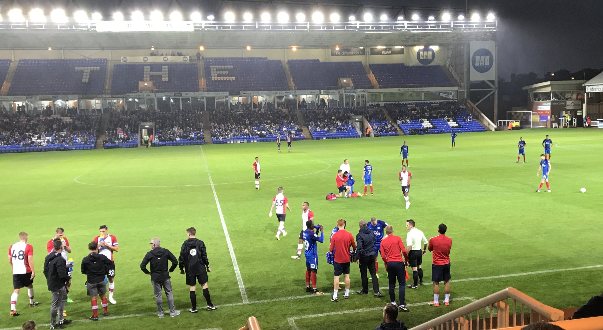 A stop in play as a Peterborough United player receives attention on the pitch, whilst Martin Hunter and Kelvin Davis offer advice to the Southampton players on the left of the picture, and Peterborough United Manager Grant McCann and Assistant David Oldfield talk with their players by the Technical area.