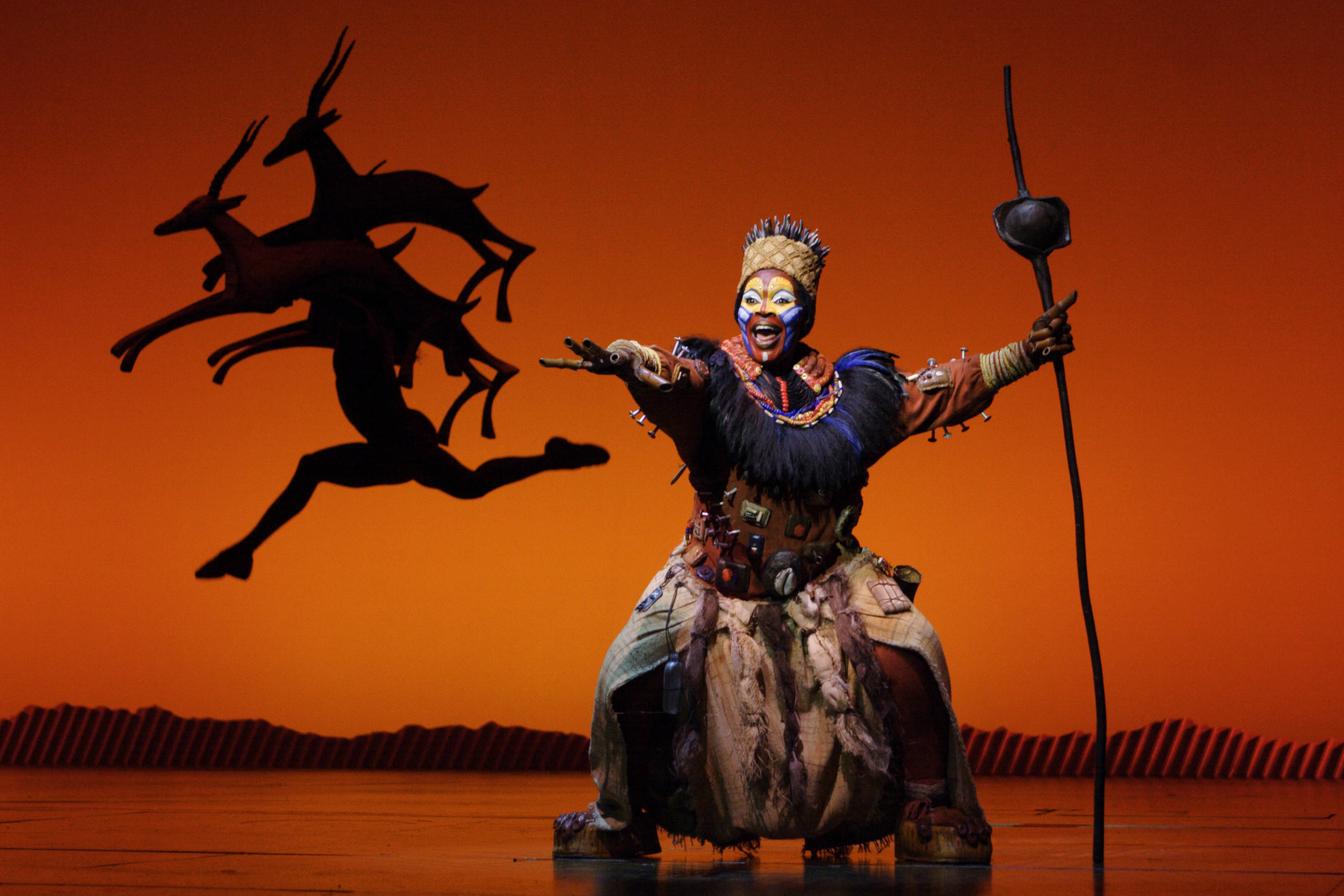 """Brown Lindiwe Mkhize as """"Rafiki"""" in the opening number """"The Circle of Life"""" from THE LION KING National Tour. Disney. Photo Credit: Joan Marcus."""