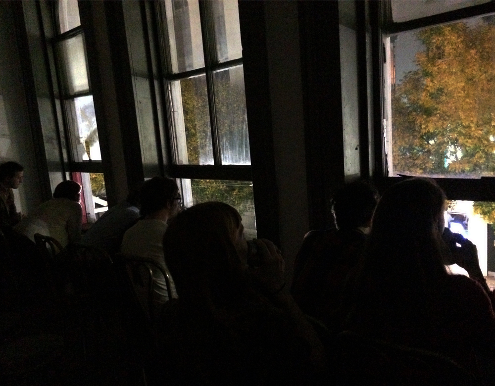 The audience watches from a second story window across the street
