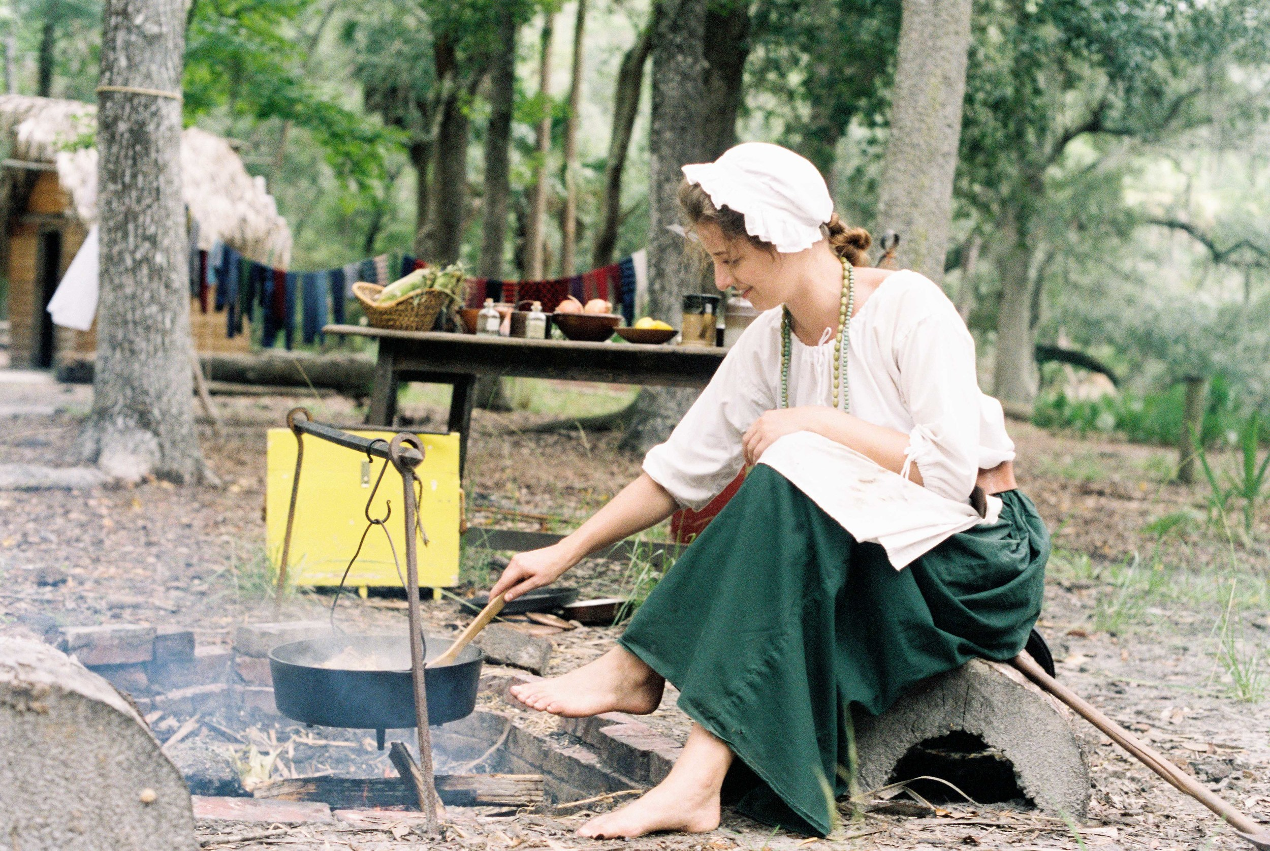 A colonial woman brewing a traditional vegetable stew.