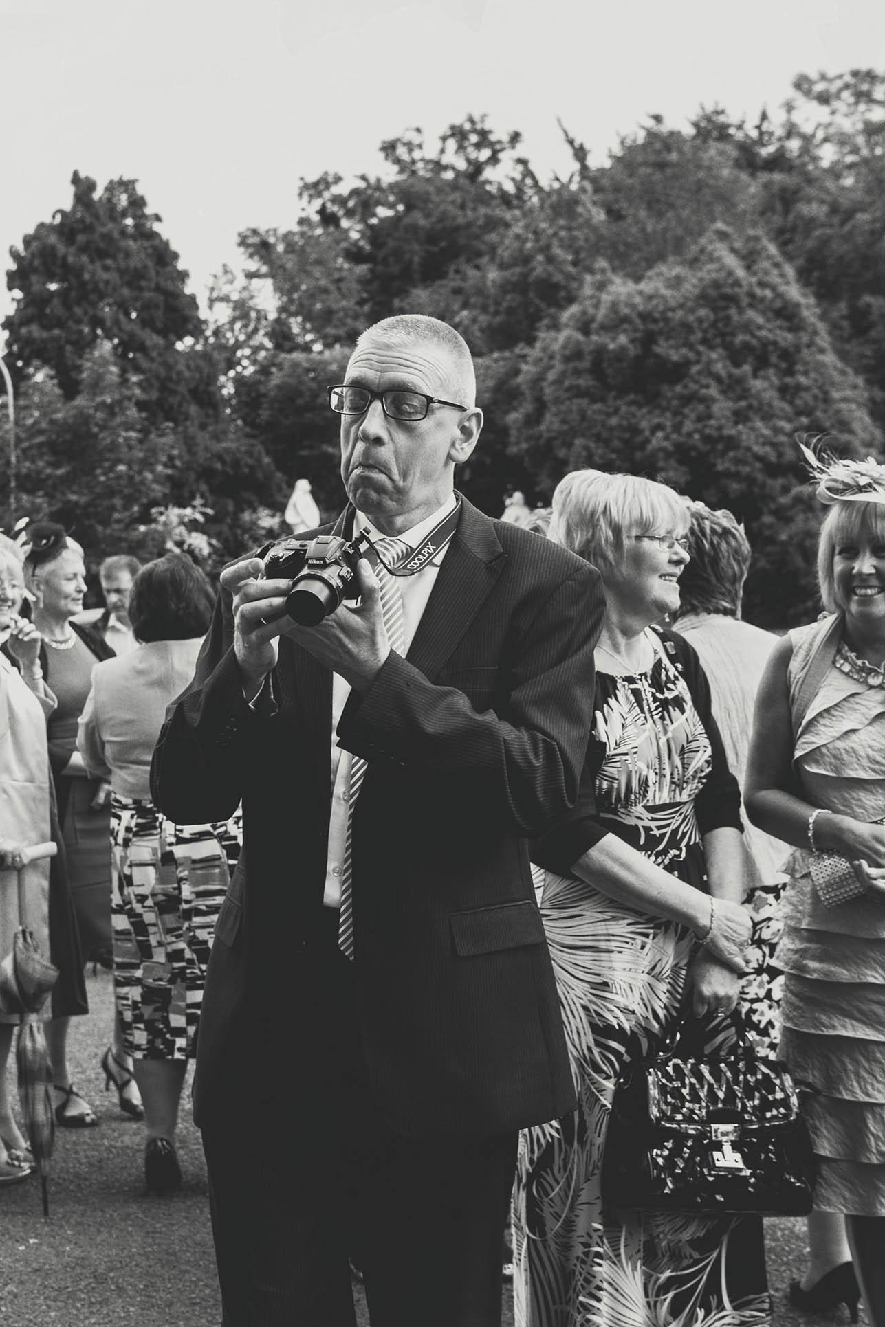 Druids Glen wedding photography, wedding guest taking a photo
