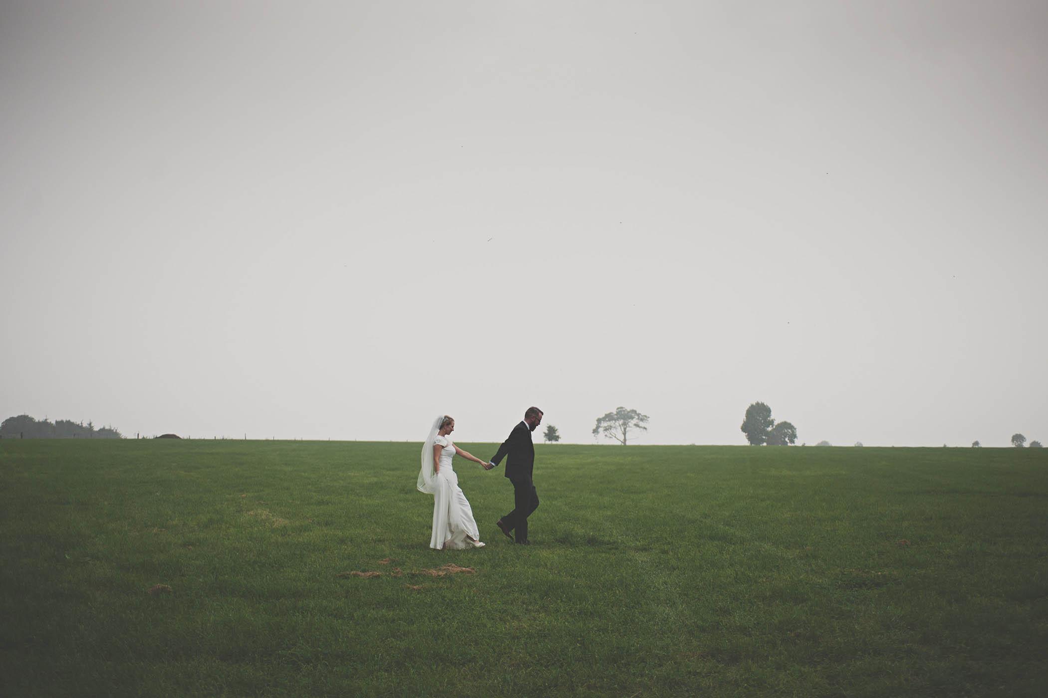 Borris House wedding couple walk through field