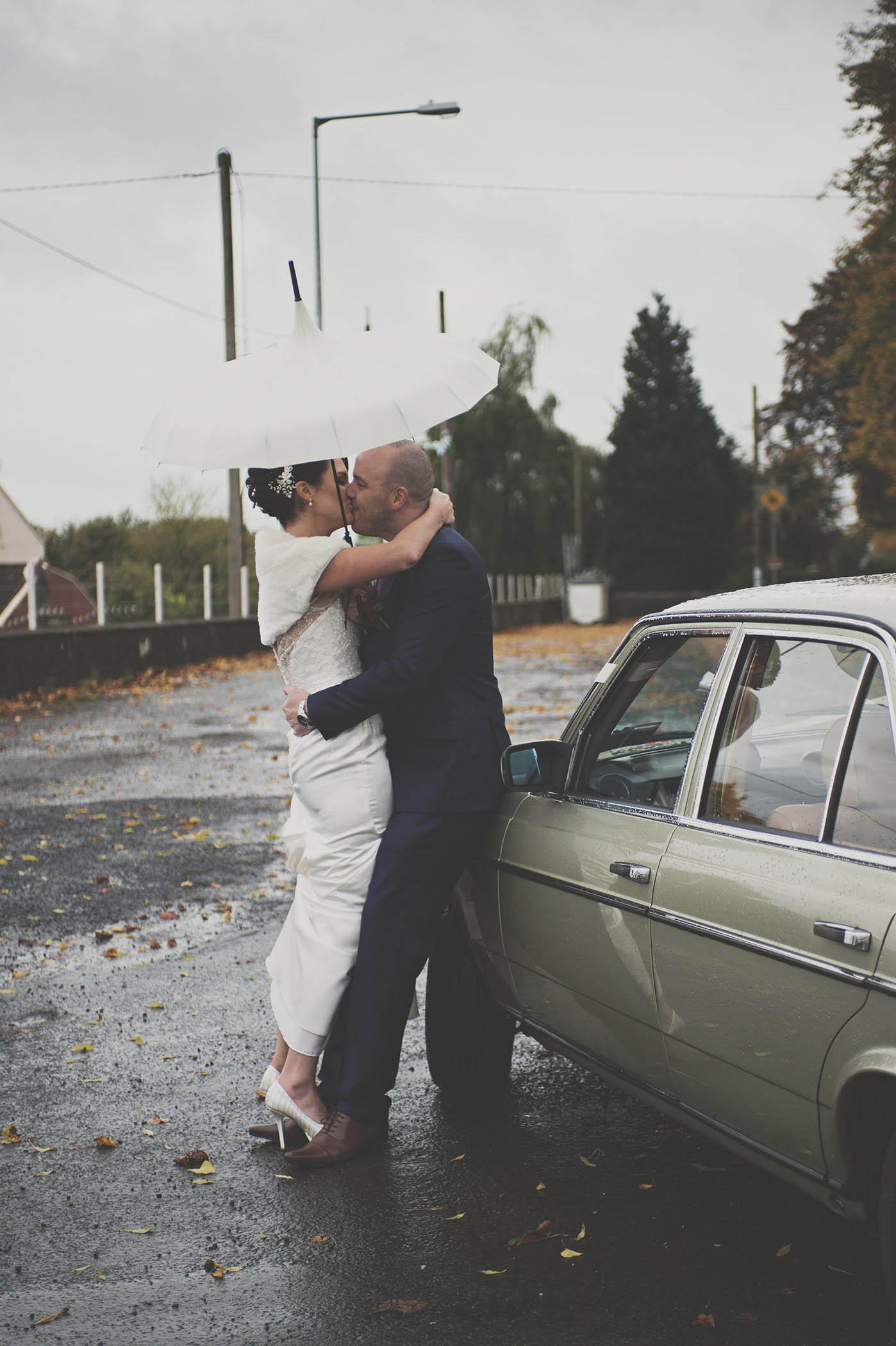 Wedding couple kiss under umbrella