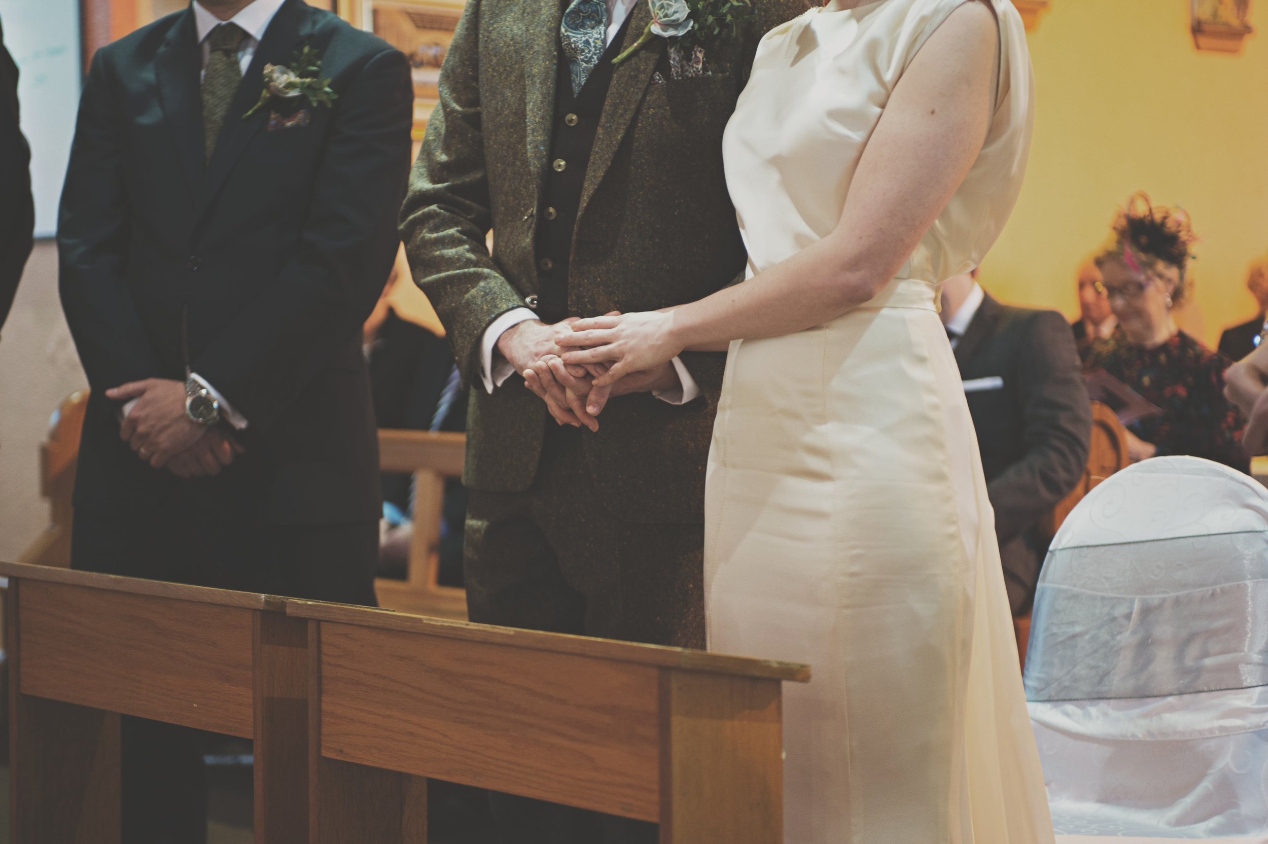 Holding hands at wedding service