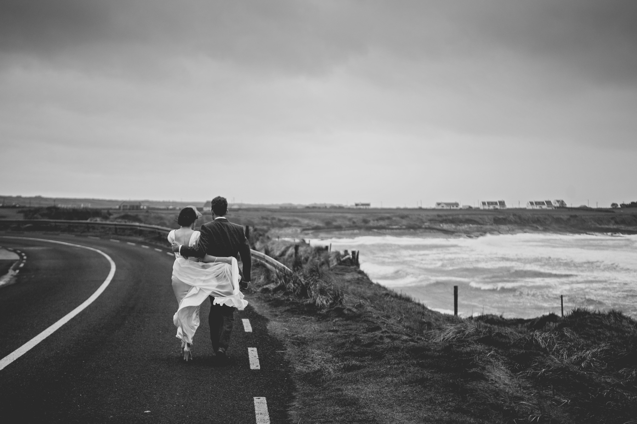Wedding couple walking the coast road in Spanish Point