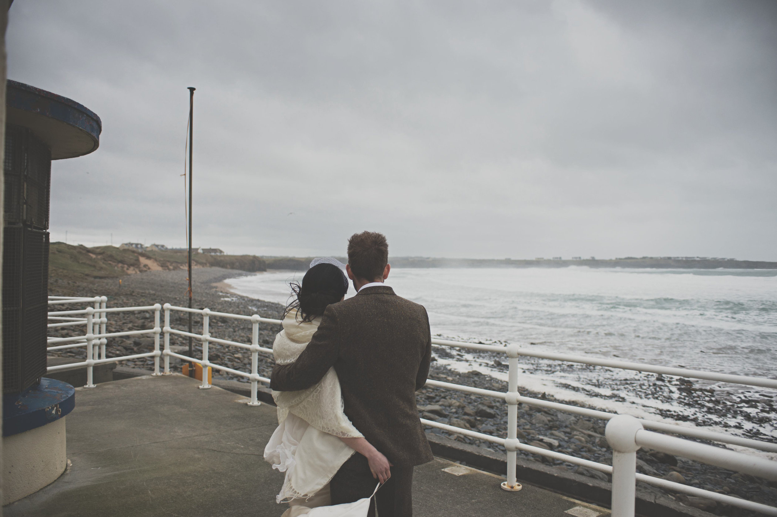 Wedding couple look out at sea, Spanish Point