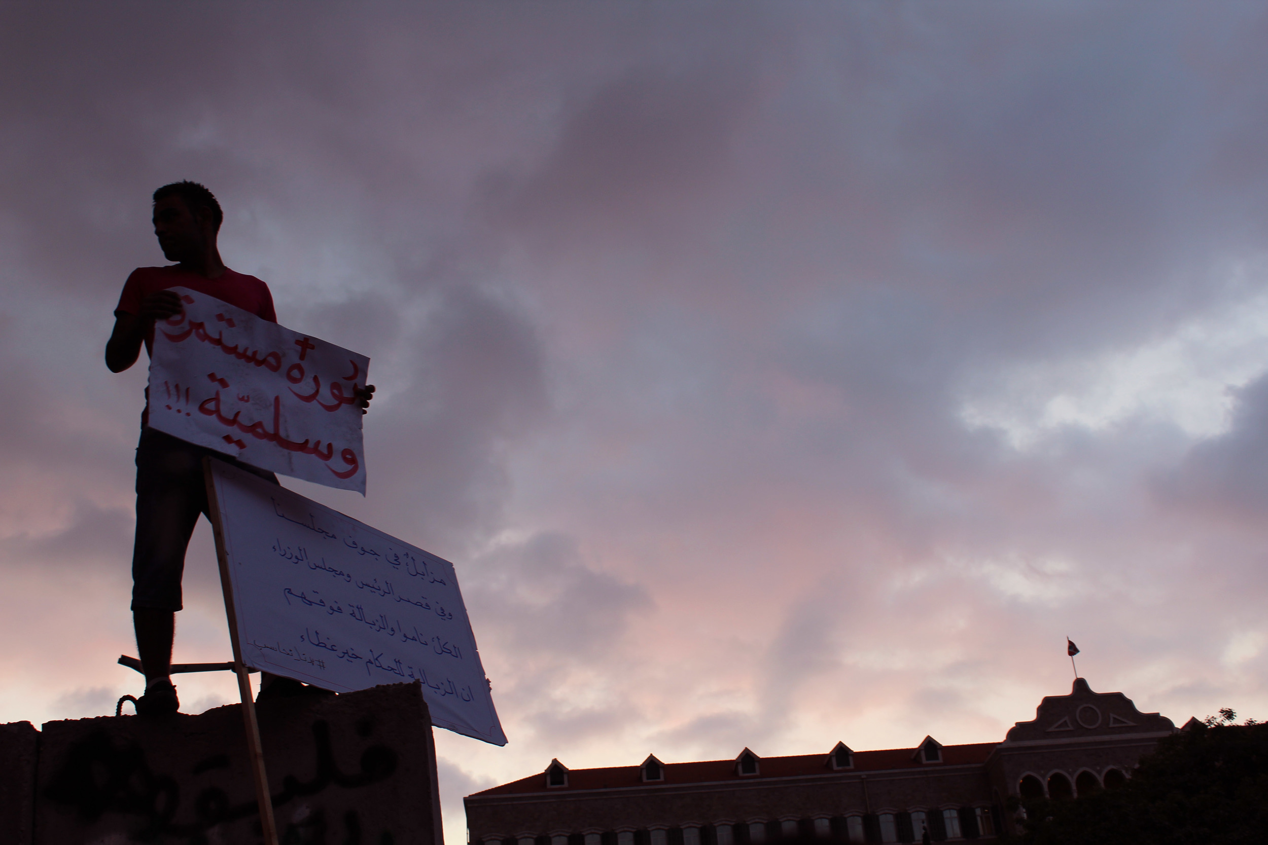 """Image: A protester in   Beirut on top of a concrete barrier near the Grand Serail in Riad Solh Square holding a sign that says, """"The revolution is ongoing and peaceful."""" Photo by Sarah Shmaitilly"""