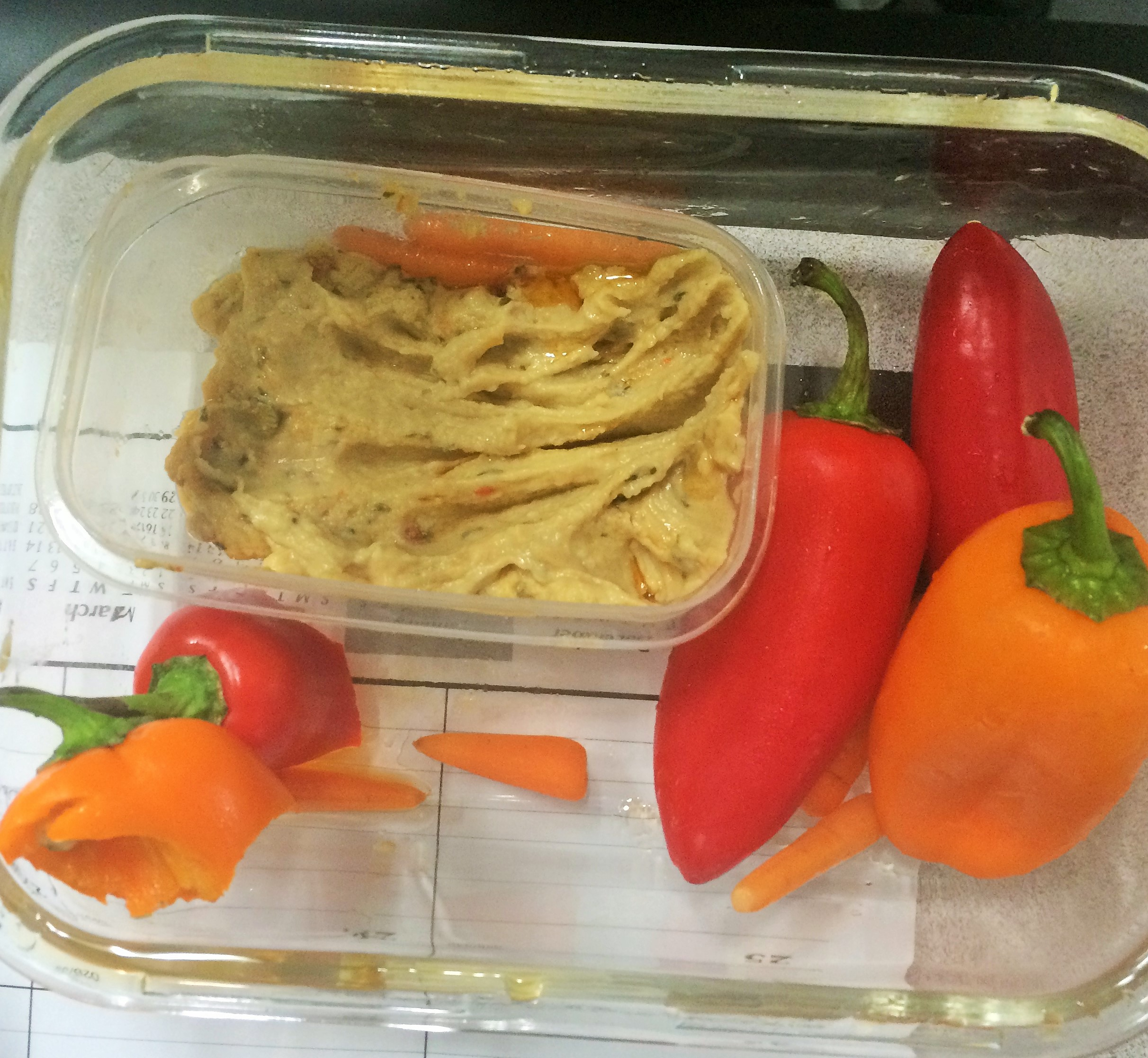 Half-eaten lunch of baby carrots, mini bell peppers and hummus