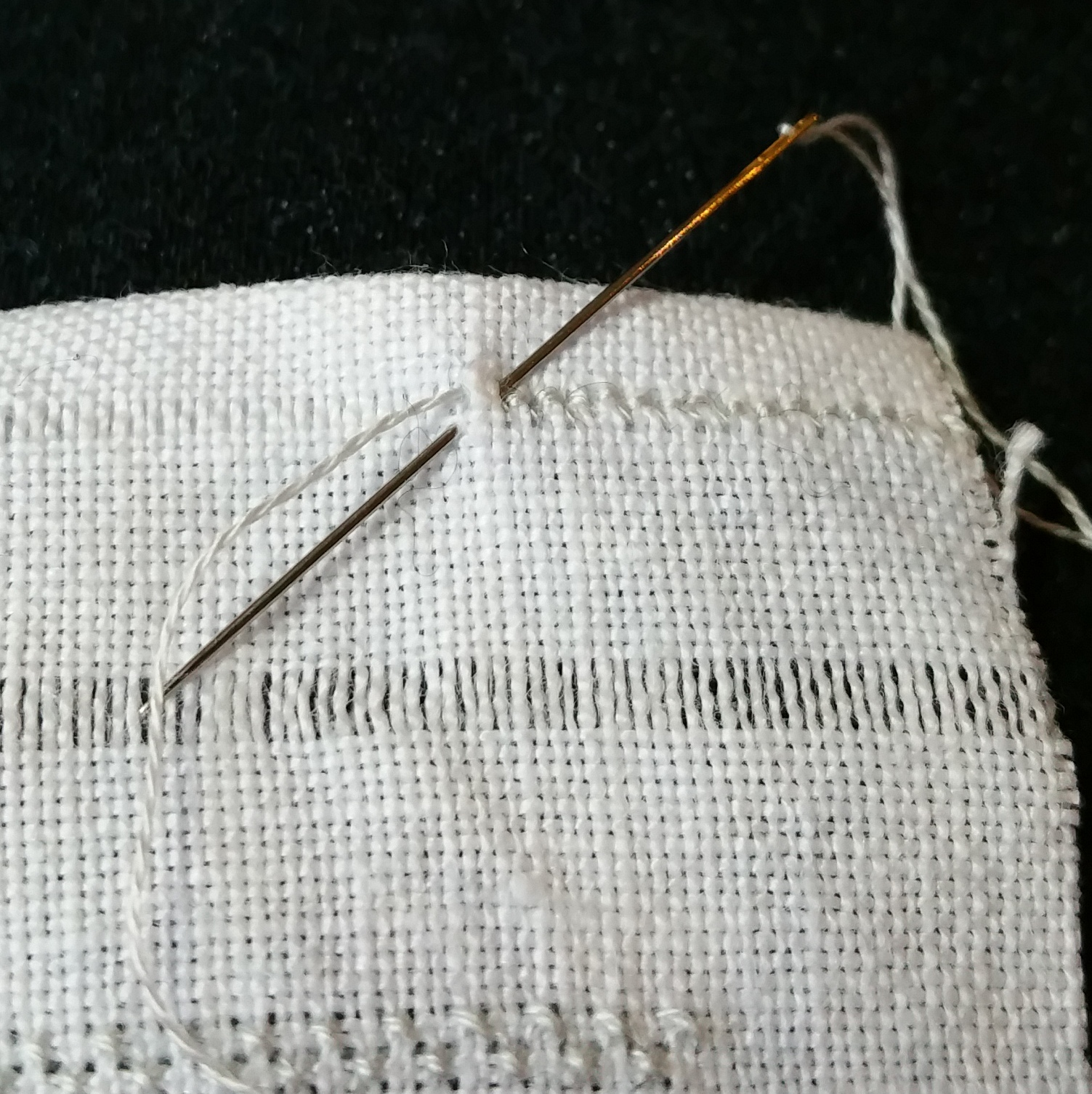 Working the hemstitch - I found it easier to change over to a sharp needle for this, since I needed to catch the bit of the folded-over fabric in my stitches.