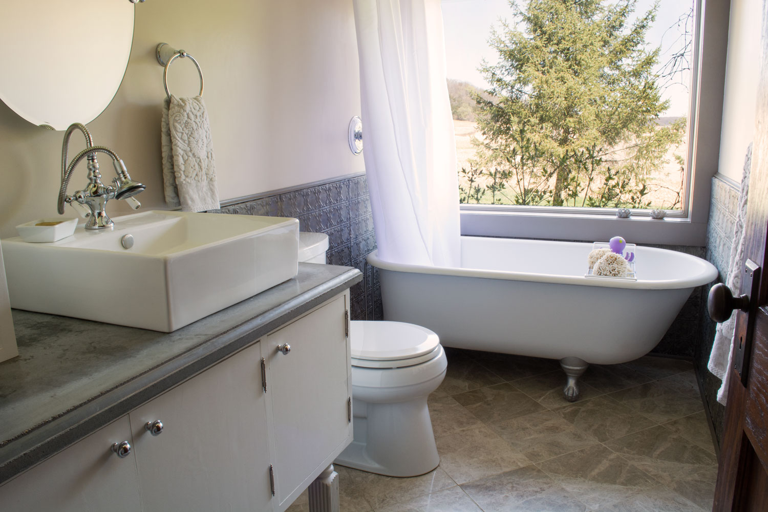 This bath is composed of many salvaged materials; the wainscoting was salvaged from an old ceiling and refinished; the tile was found in a remnant warehouse. The window, which helps the narrow room feel wider, was at a local ReStore, and the tub was salvaged locally and refinished. Counters are concrete.