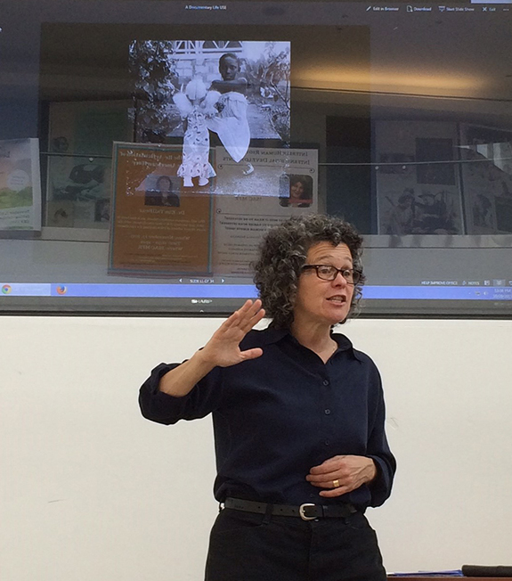 "Ellen Frankenstein, gives a talk at Galluadet University as part of the tour.. She's projecting an image called ""Kim with a Doll"" from a documentary still series made in Barbados. Photo by Brian Greenwald."