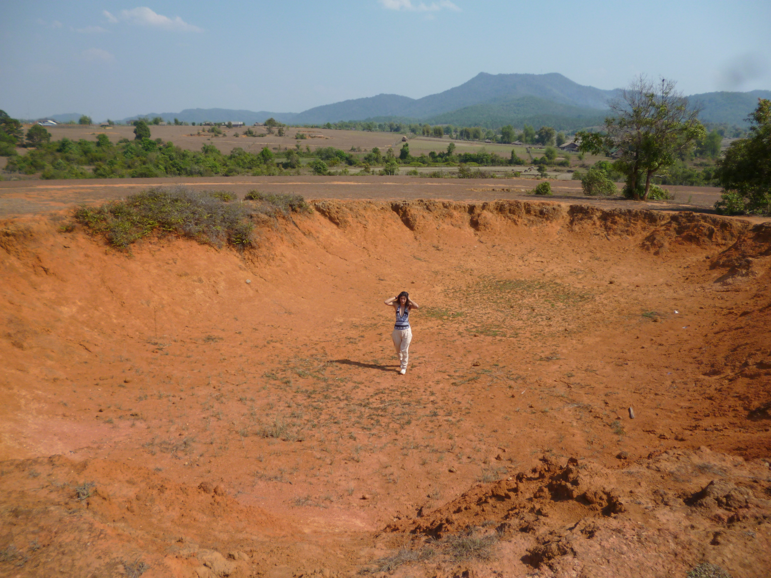 Dilara exploring a bomb crater she found near the Plain of Jars, Laos