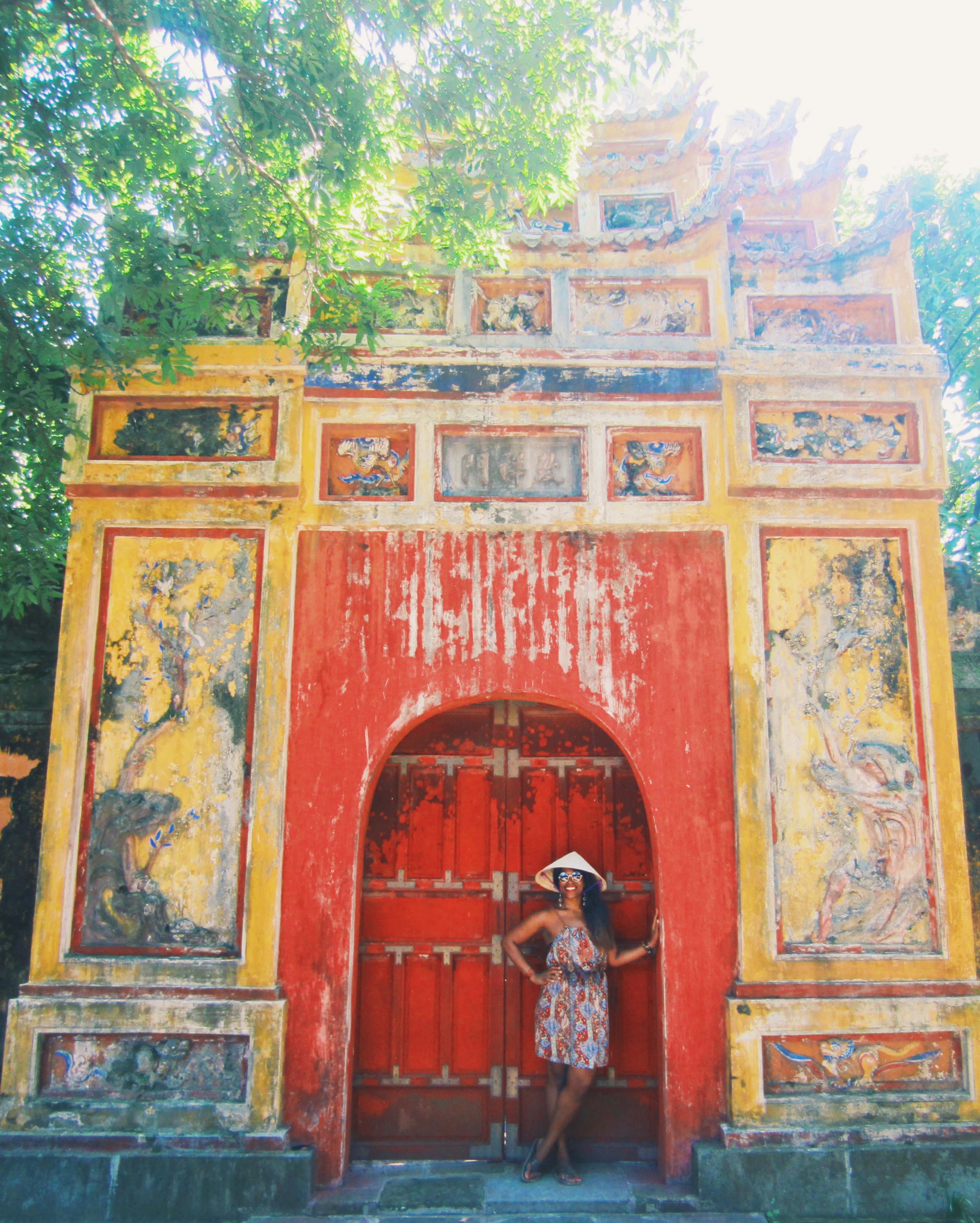 Glo in front of a traditionally decorated door in Hue, Vietnam
