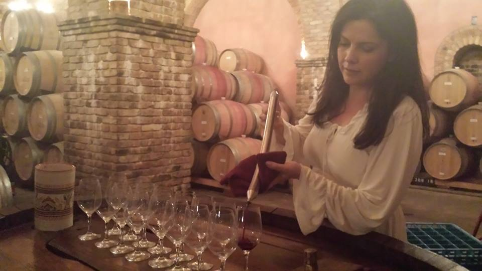 Louree testing some of the wine barrels in her region of Tuscany