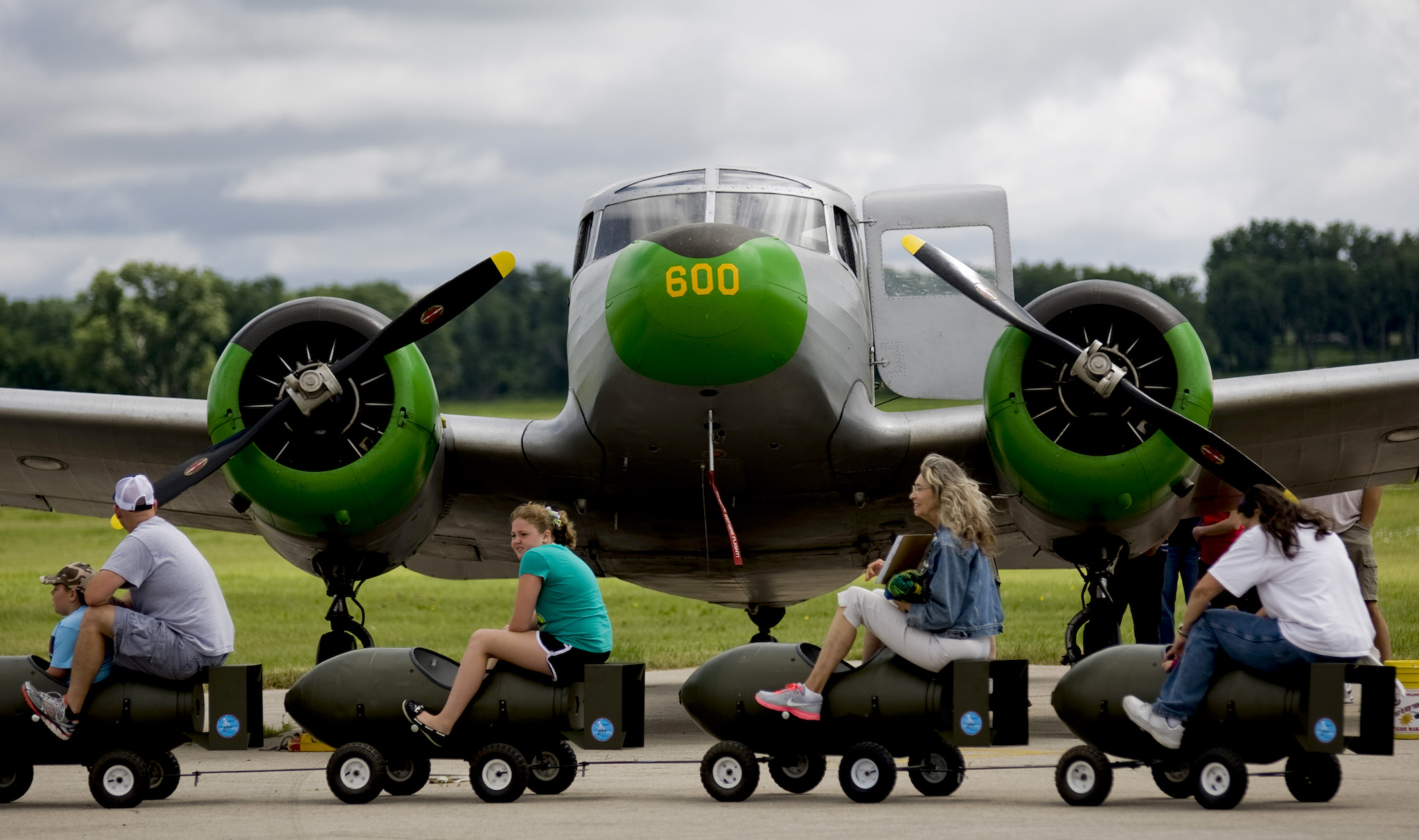 People on a wagon ride roll in front of a Cessna UC-78 Bobcat at the Commemorative Air Force Fly In event at Hutchinson Airport on Saturday, June 7, 2014, in Hutchinson, Kansas. The event included vintage aircraft, music, games and displays.