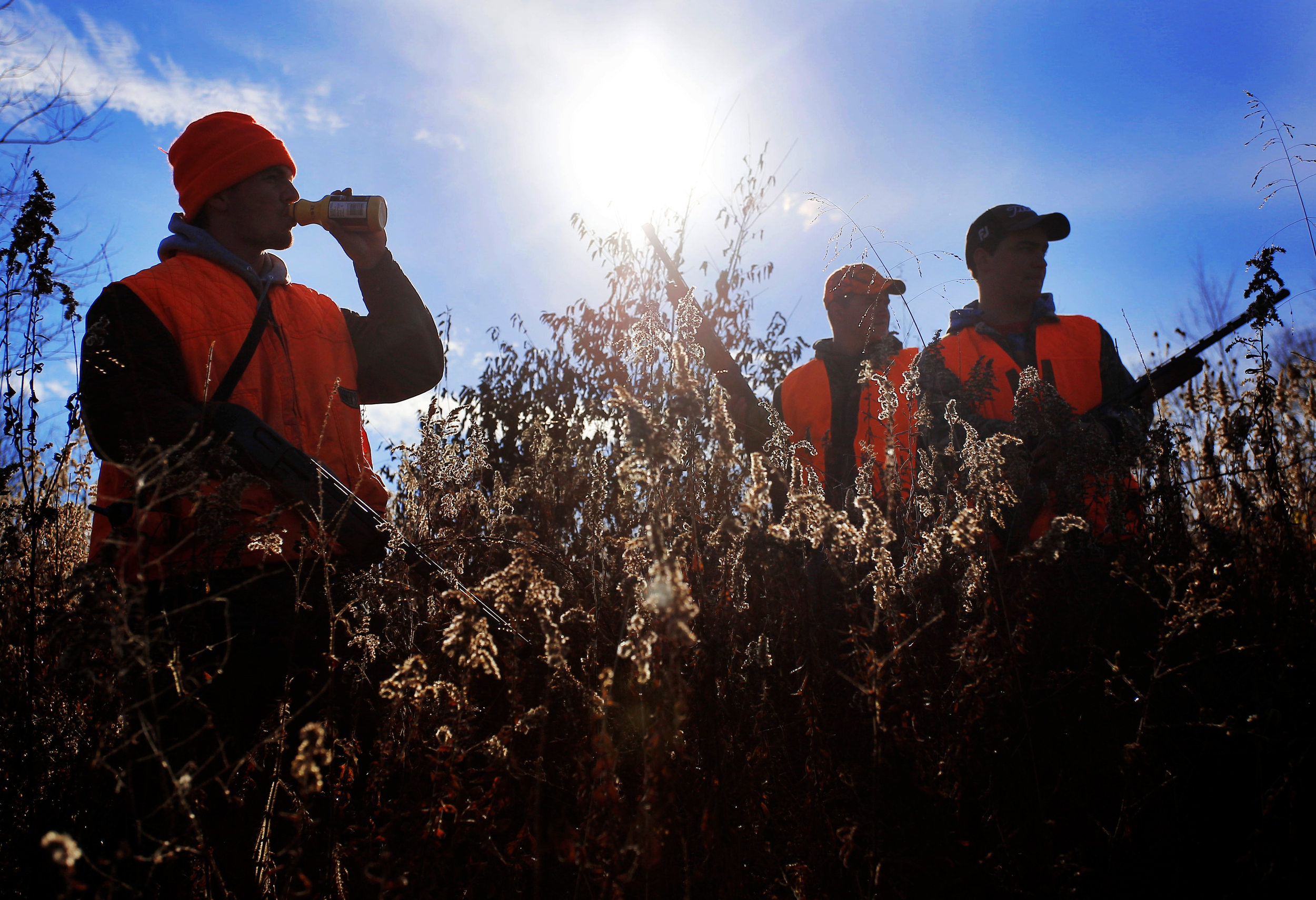 Jacob Koons drinks some milk while taking a break with Bryce Smathers, center and Reed Morgan while rabbit hunting in a field outside of Millfield, Ohio, on November 11, 2014.
