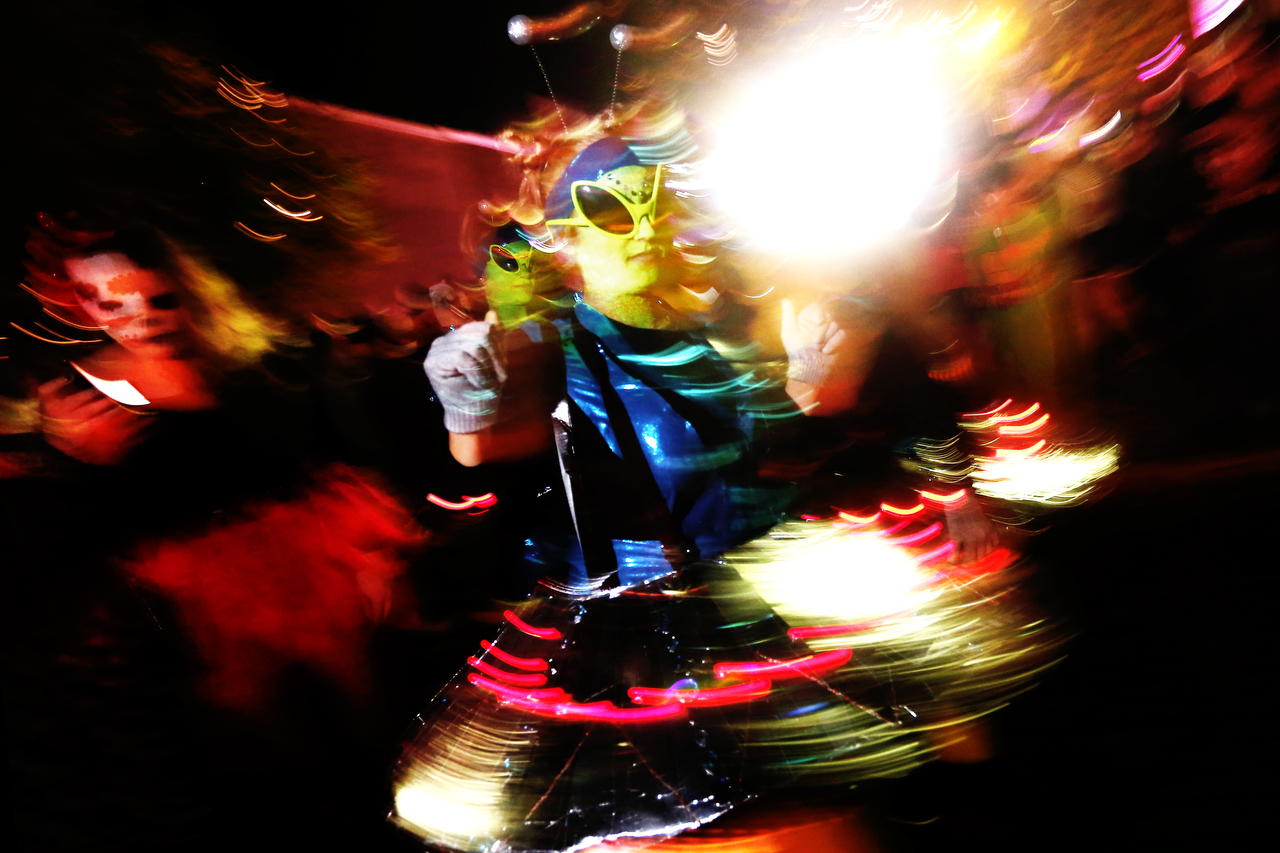 A woman dressed in an alien costume dances on Court Street during the annual Halloween Block Party in Athens, Ohio.