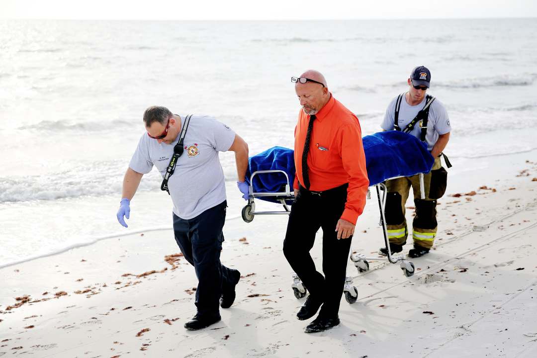 Collier County Coroners remove a corpse that washed ashore at Vedado Beach in Naples, Florida, on Monday, July 12, 2015.