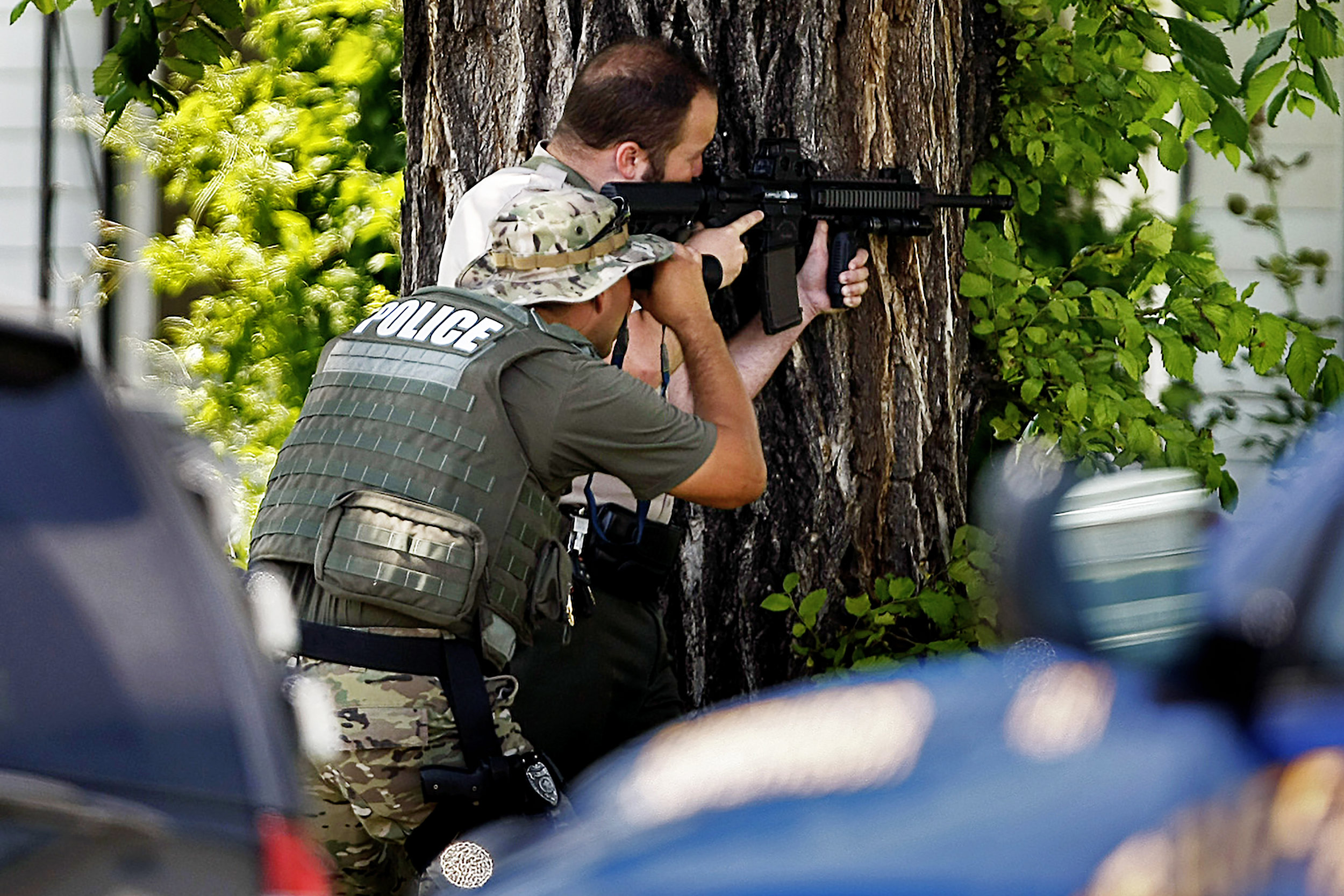Police SWAT officers keep an eye on the alley where Thomas Fee, 52, of Hutchinson, barricaded himself in a garage with a gun, causing a standoff with police on July 4, 2014, in Hutchinson, Kan. Fee was eventually taken into custody after two attempts at flooding him out with tear gas.
