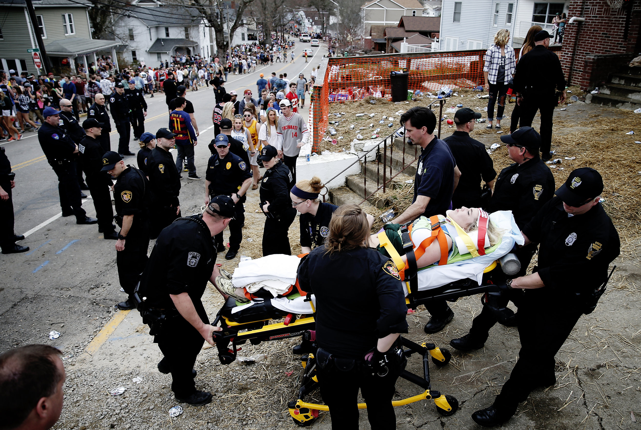 A woman is rescued by emergency responders after falling from a porch during the annual Mill Fest block party in Athens, Ohio.