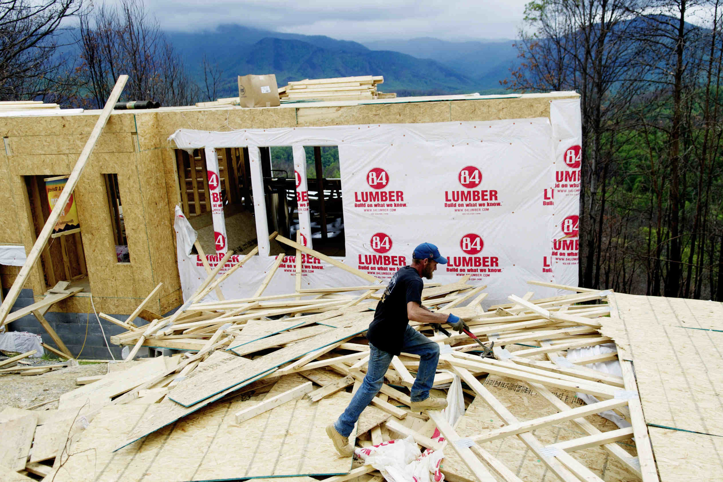 Ed Call, of American Home Builders, works on removing old roofing material that blew off of Glenn Warren's new home under construction on Wiley-Oakley Drive after a strong windstorm hit the area in Gatlinburg, Tennessee on Friday, May 5, 2017.
