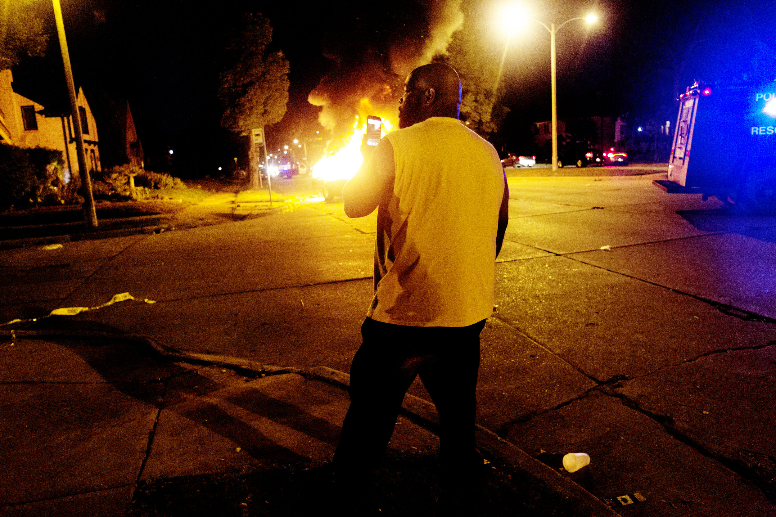 A bystander watches as an automobile burns at the scene of a riot on Sherman Boulevard and Auer Street in Milwaukee, Wisconsin on August 13, 2016. The riot was the result of heated confrontations between police and protestors after an unarmed man was shot and killed by a police officer earlier in the day.